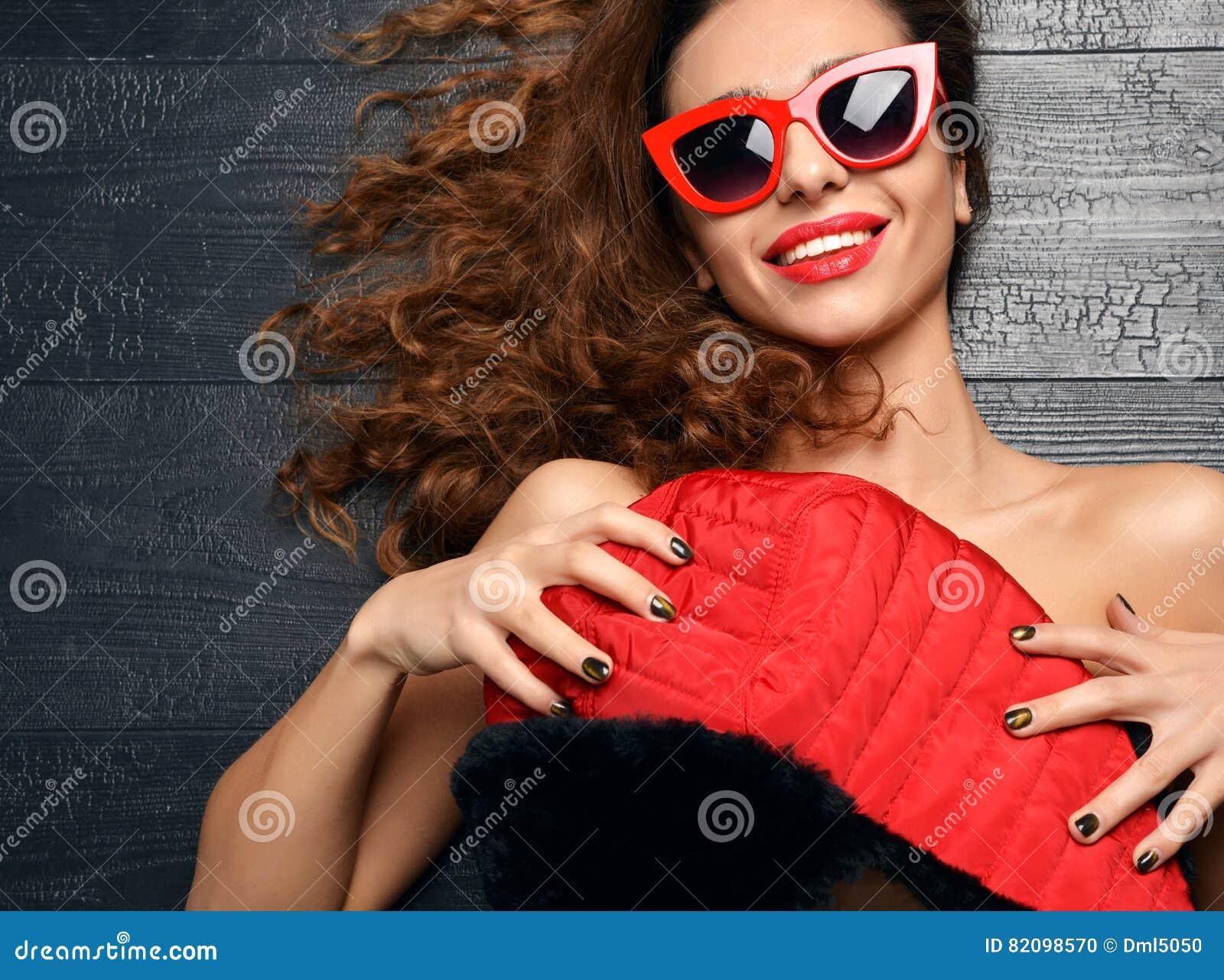 Kobiety lying on the beach w lato mody okularach przeciwsłonecznych śmia się czerwone wargi i w