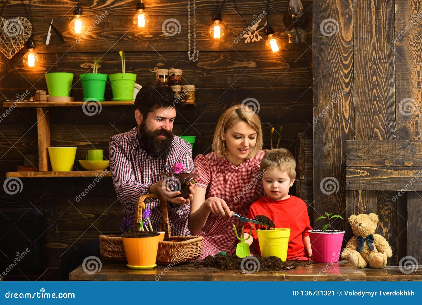 Kobiety, mężczyzny i chłopiec dziecko, kocha naturę Kwiat opieki podlewanie Glebowi użyźniacze Rodzinny dzień charcica Szczęśliwy