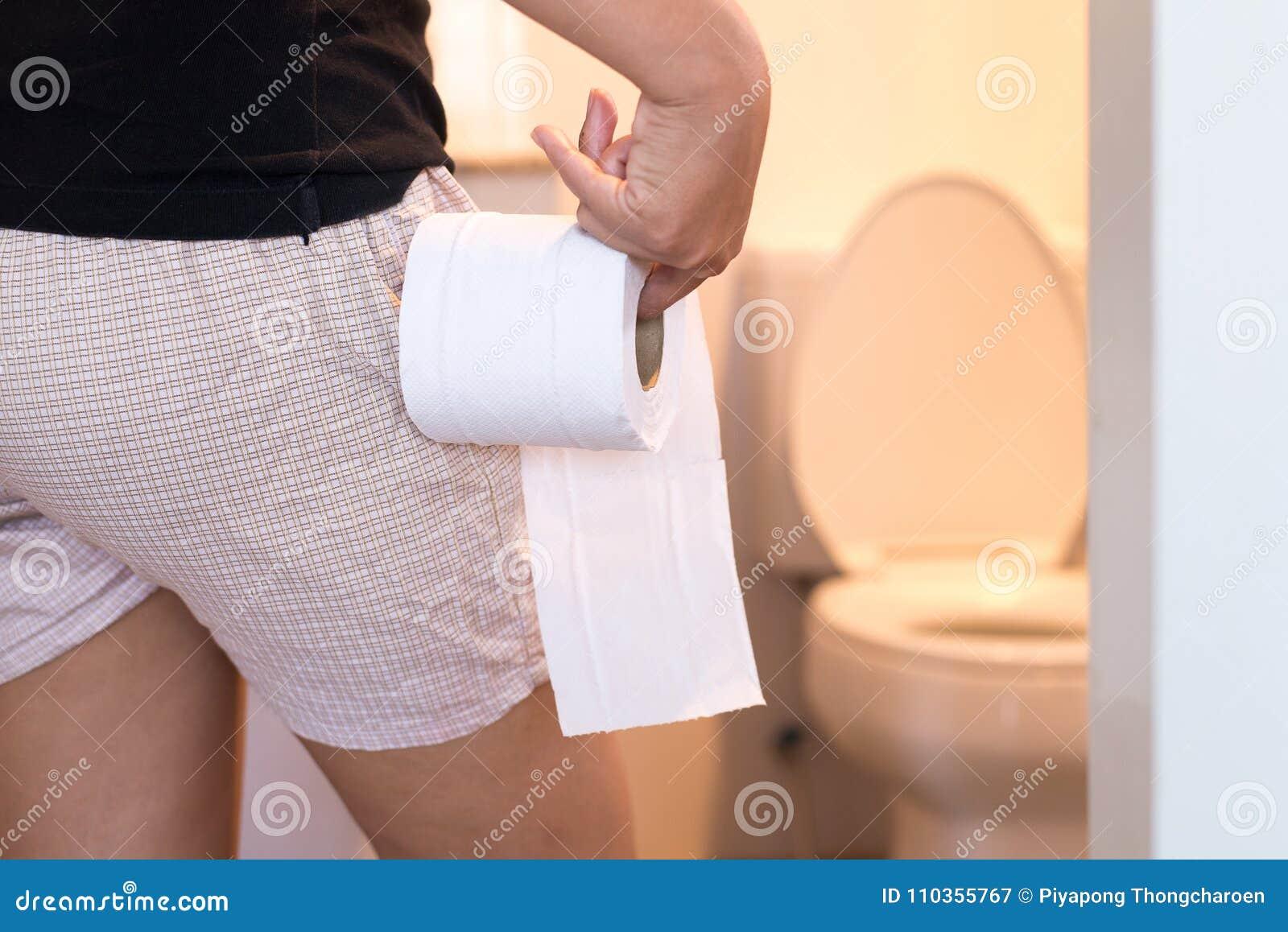 Kobiety mienia papier toaletowy i używać łazienka w ranku