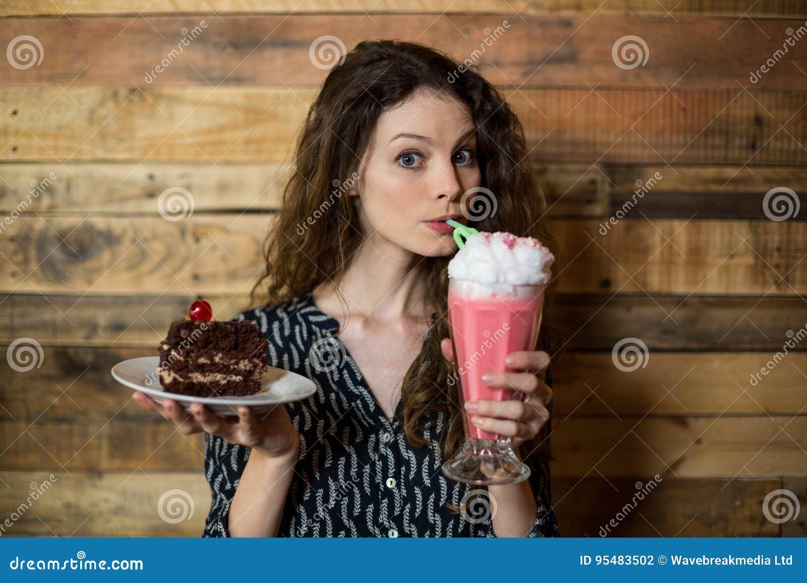 Kobiety mienia talerz ciasto i pić milkshake z słomą