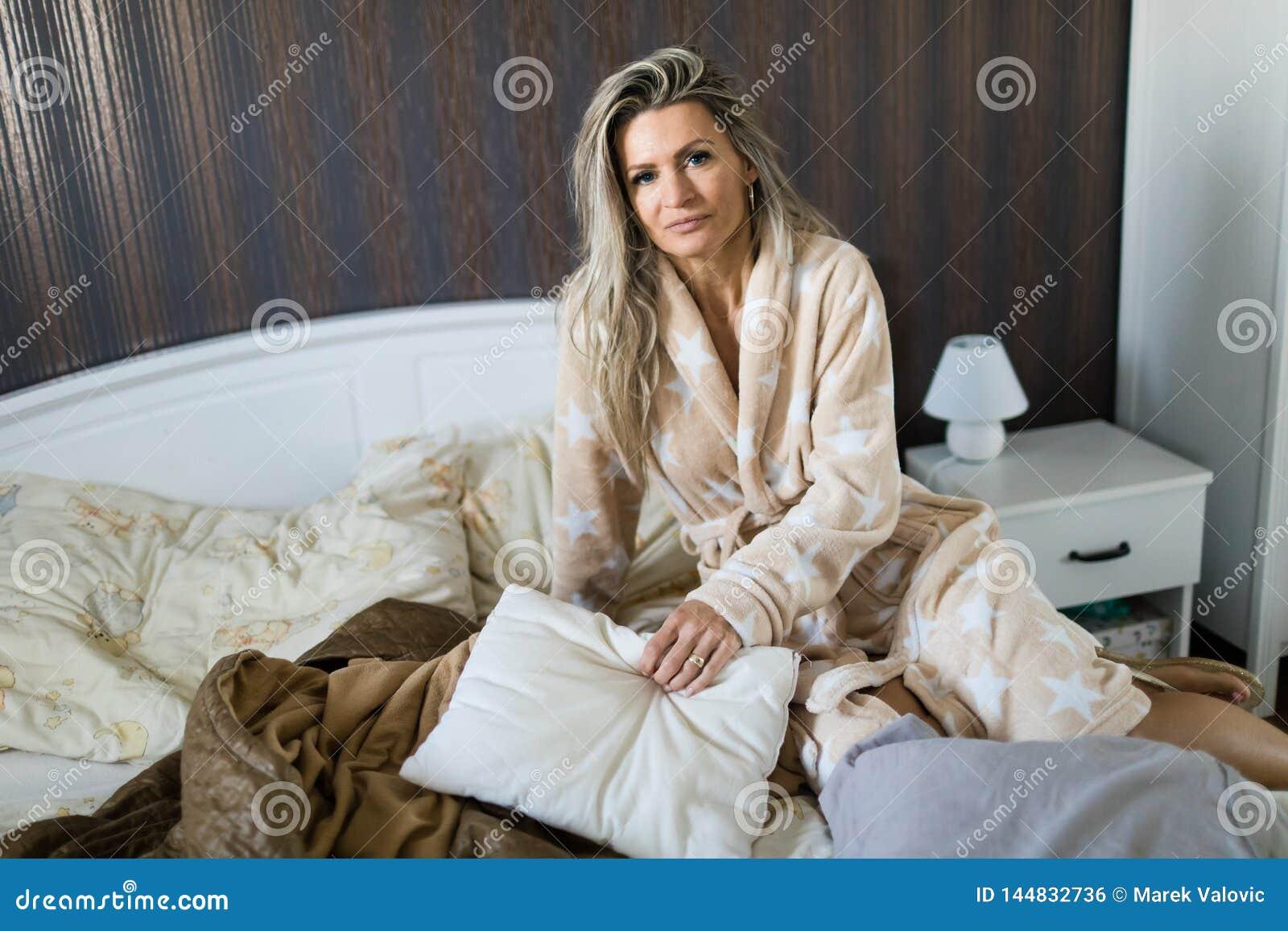 Kobiety obsiadanie na łóżku jest ubranym opatrunkową togę
