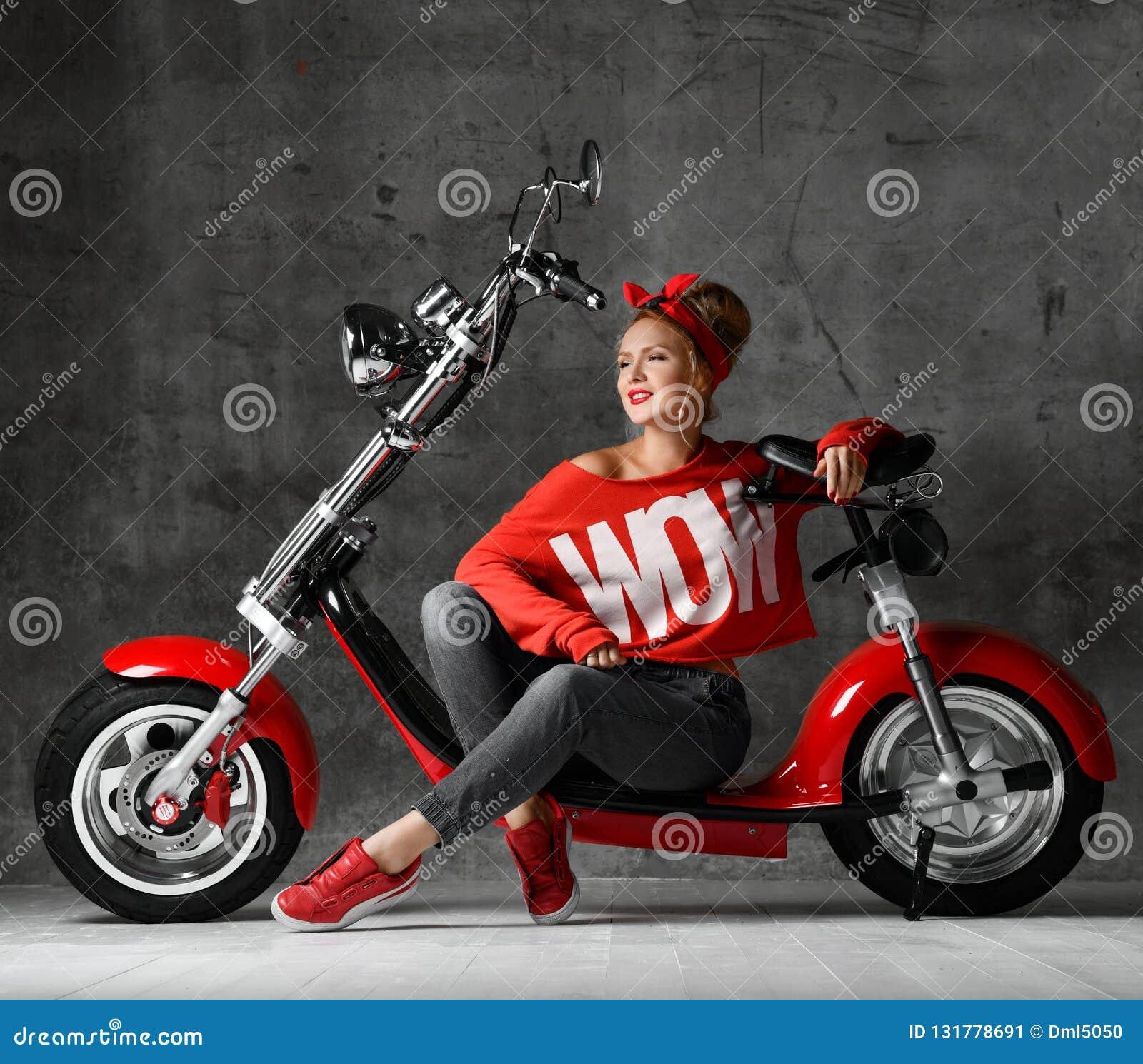 Kobiety obsiadanie na motocykl rowerowej hulajnogi pinup retro stylu w czerwonej bluzce i cajgach