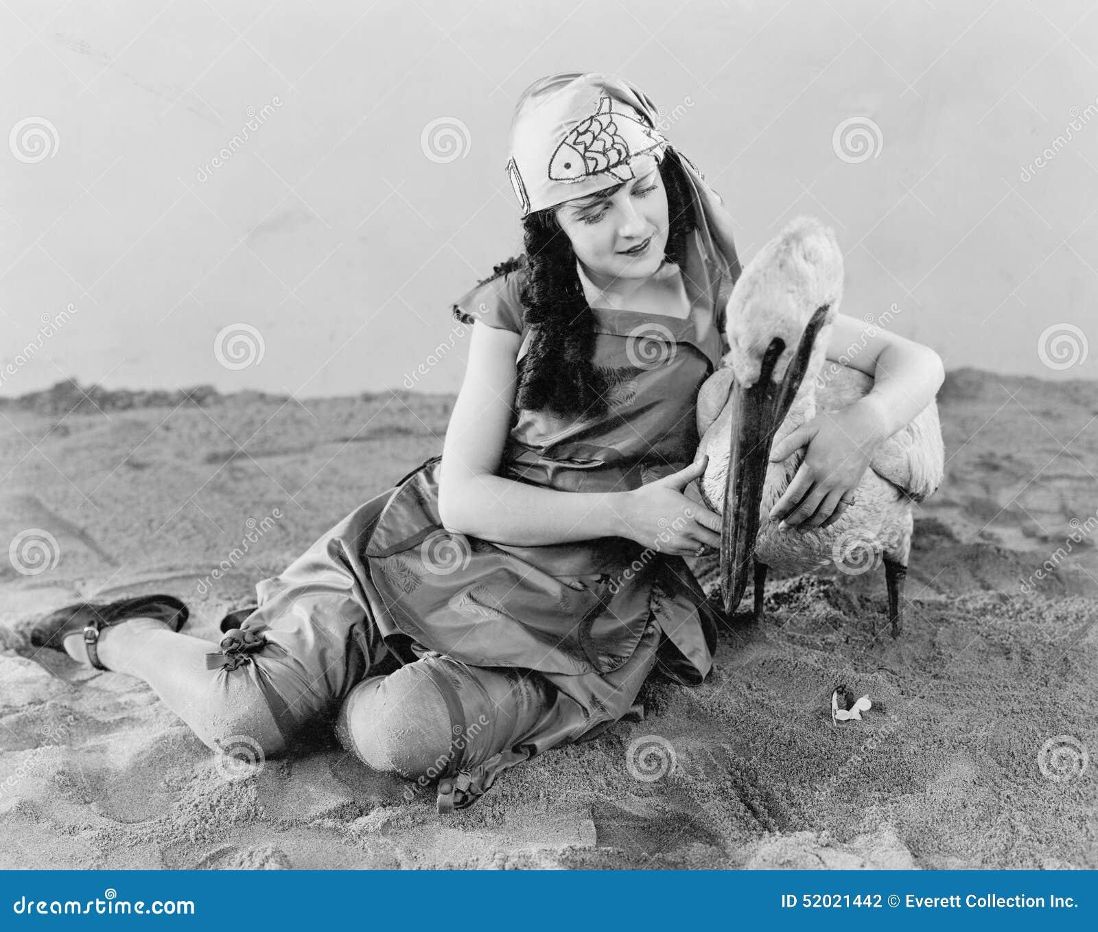 Kobiety obsiadanie na zmielonym mieniu pelikan w jej ręce (Wszystkie persons przedstawiający no są długiego utrzymania i żadny ni