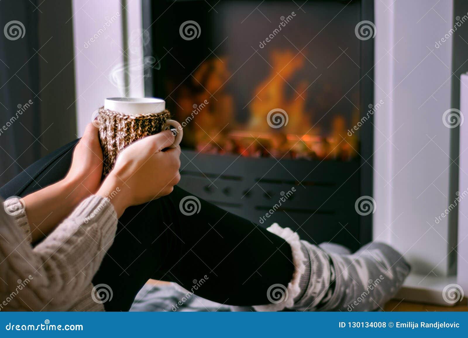 Kobiety obsiadanie przed graby i mienia filiżanką herbata w ręce na nogach