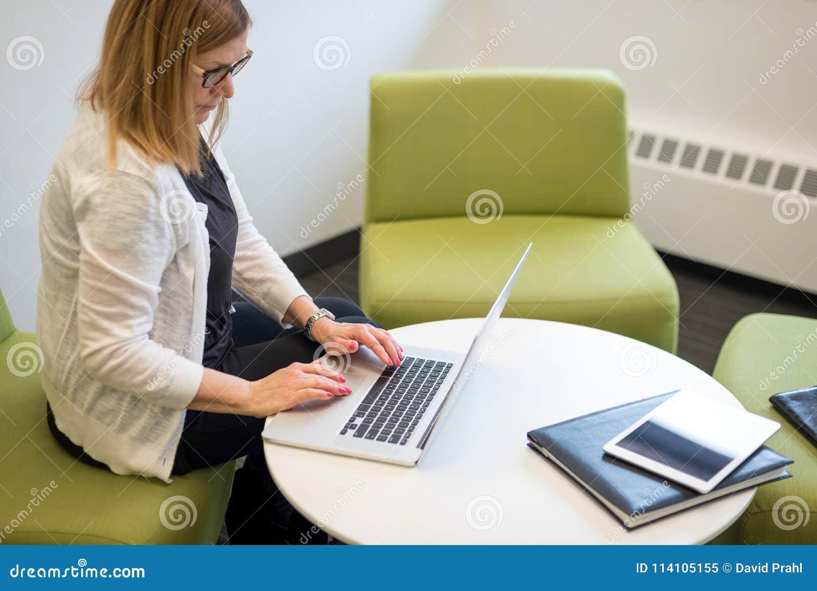 Kobiety obsiadanie w nowożytnym workspace pisać na maszynie na laptopie