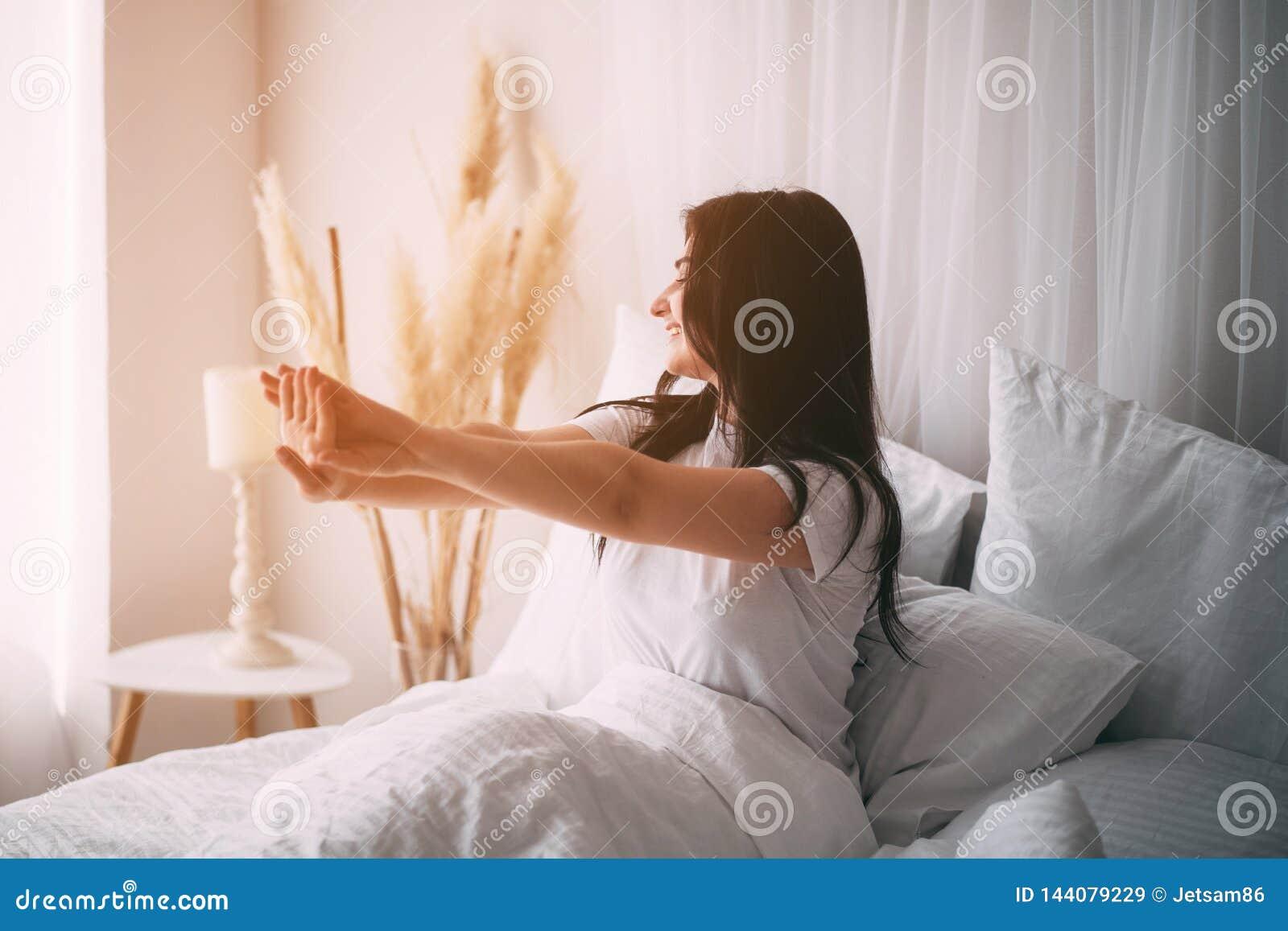 Kobiety obudzenia rozciąganie w łóżku w wczesnym poranku