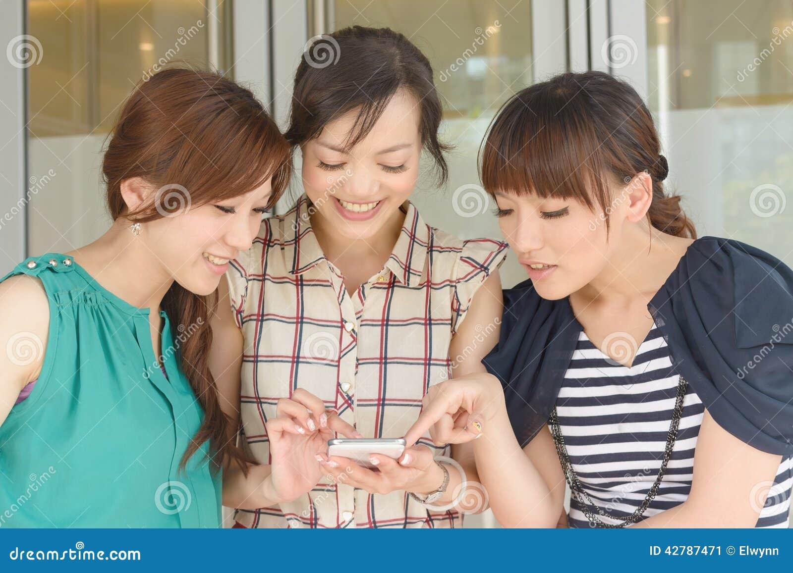 Kobiety patrzeje coś na telefonie komórkowym