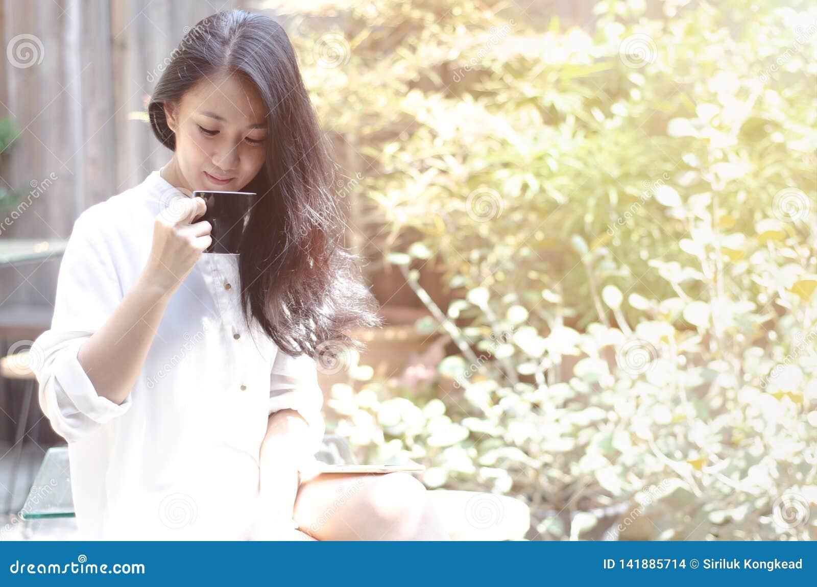 Kobiety Pije kawę w ogródzie w ranku