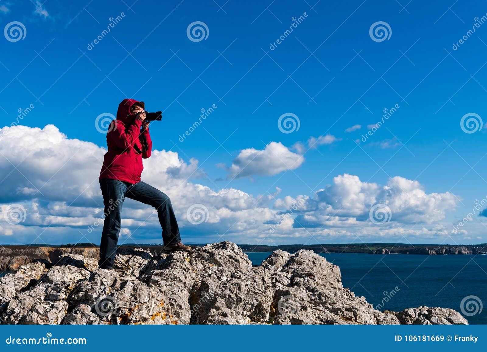 Kobiety pozycja na skale i brać fotografiach