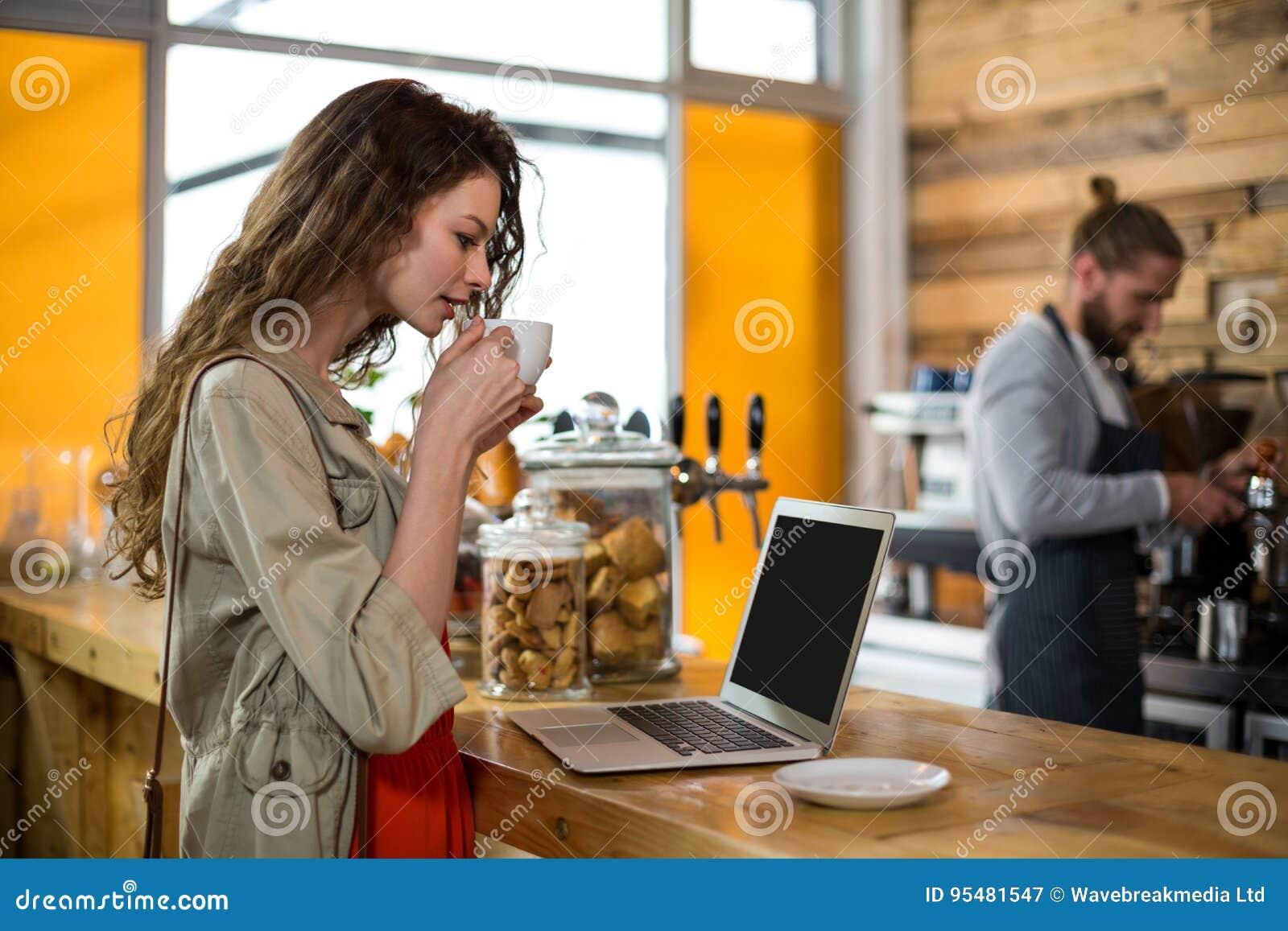 Kobiety pozycja przy odpierającym i używa laptopem podczas gdy mieć kawę