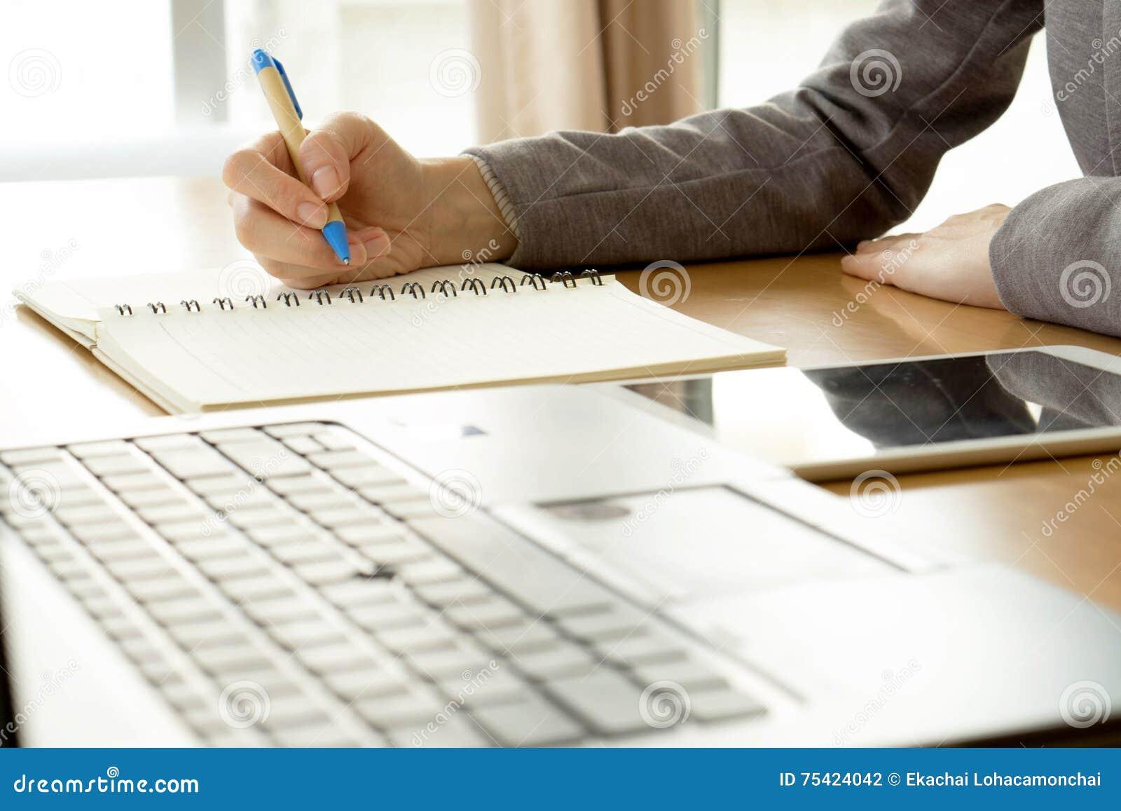 Kobiety pracującej writing na papierowym i pisać na maszynie na laptopu com