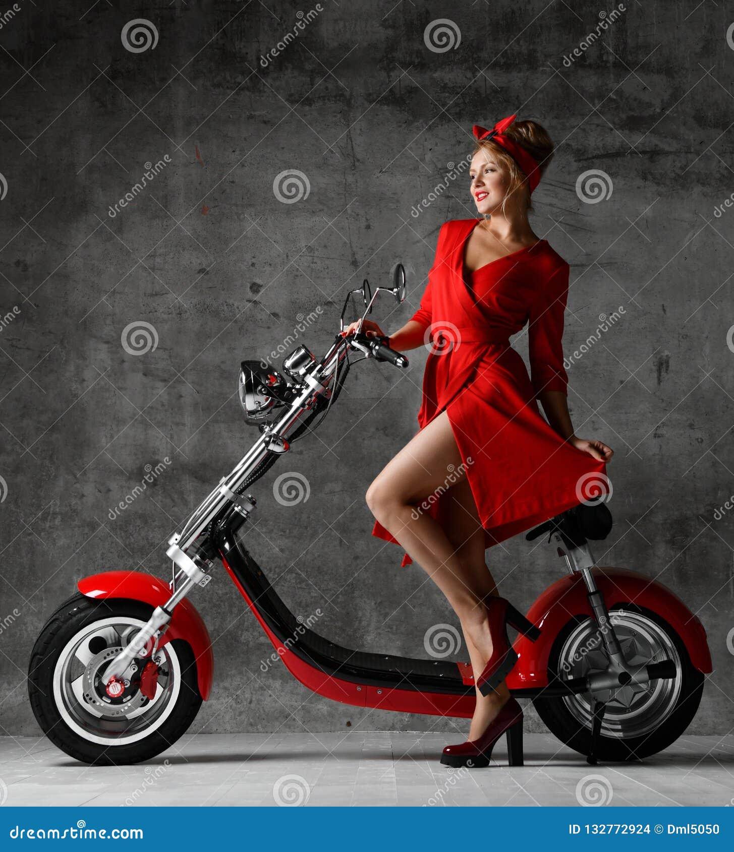 Kobiety przejażdżka siedzi na motocykl hulajnogi rowerowego pinup czerwieni retro stylowej roześmianej uśmiechniętej sukni