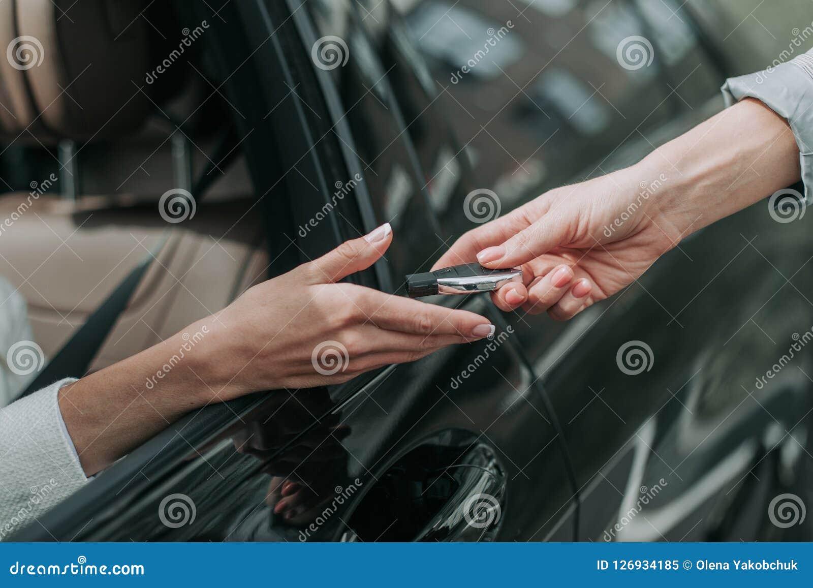 Kobiety ręka bierze klucz od samochodu sprzedawcy