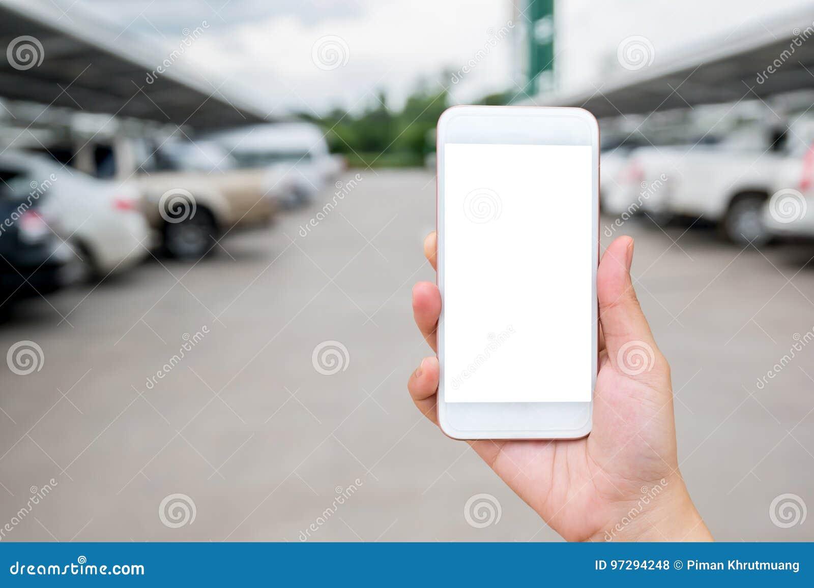 Kobiety ręka pokazuje mądrze telefon na zamazanym samochodzie w parking