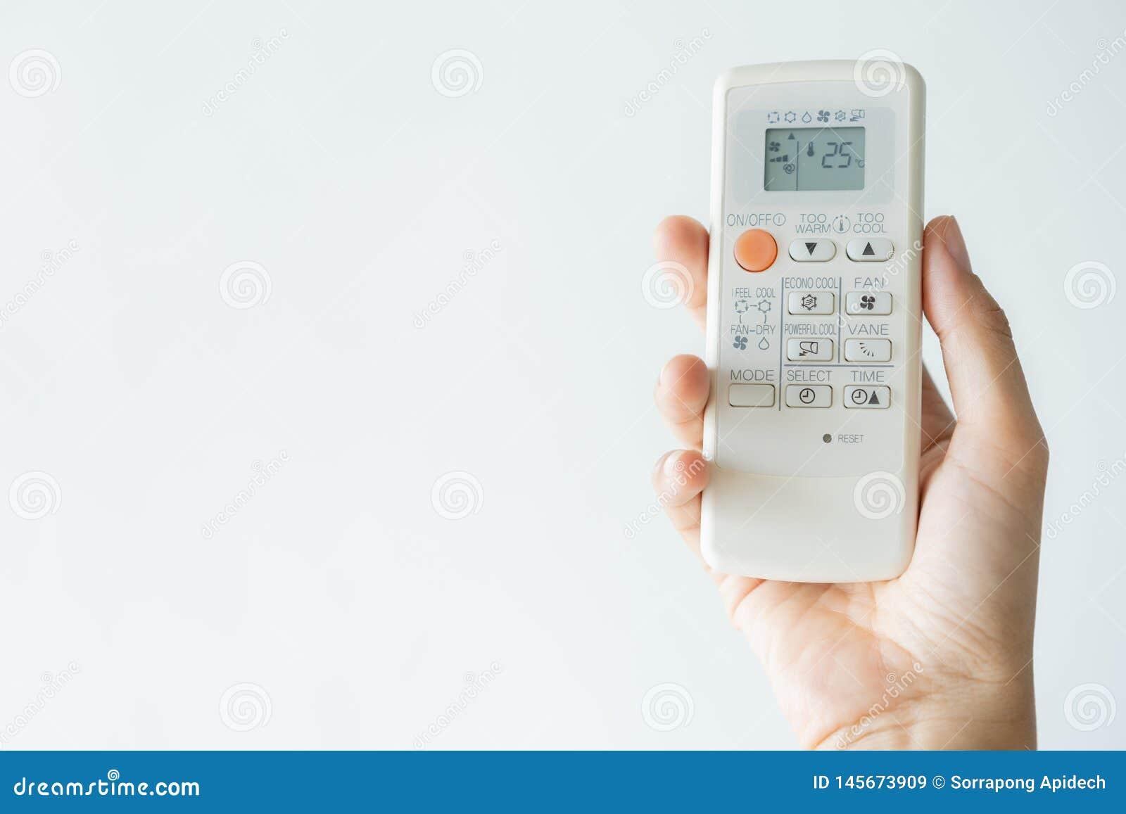 Kobiety ręka używać pilota do tv na wolnym powietrzu uwarunkowywać 25 stopni Na wolnym powietrzu 25 stopni, jest temperaturowy