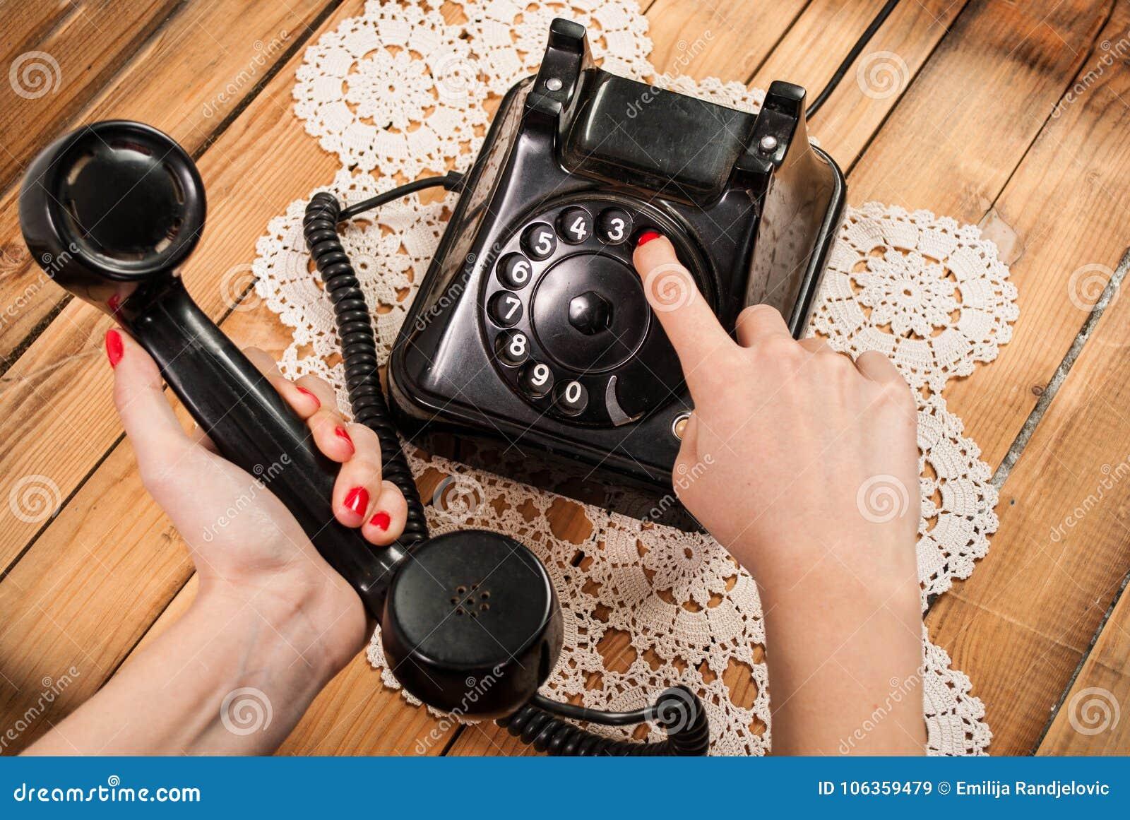 Kobiety ręka wybiera numer liczbę na starym telefonie na koronkowych tablecloths i drewnianym tle