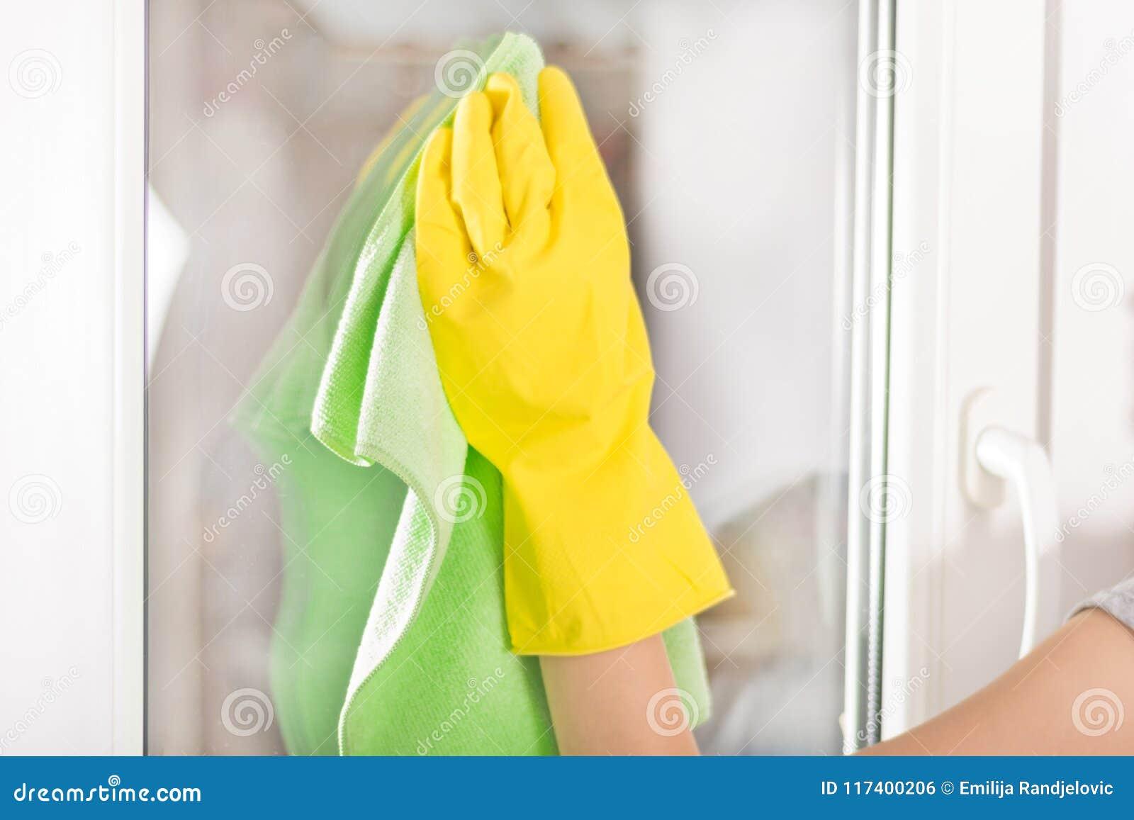 Kobiety ręka z żółtym ochronnej rękawiczki i zieleni cleaning gałganianym okno w domu