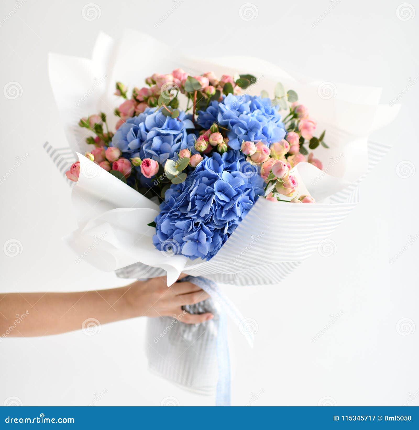 Kobiety ręki chwyta bukiet błękitni hortensja kwiaty i różowe róże