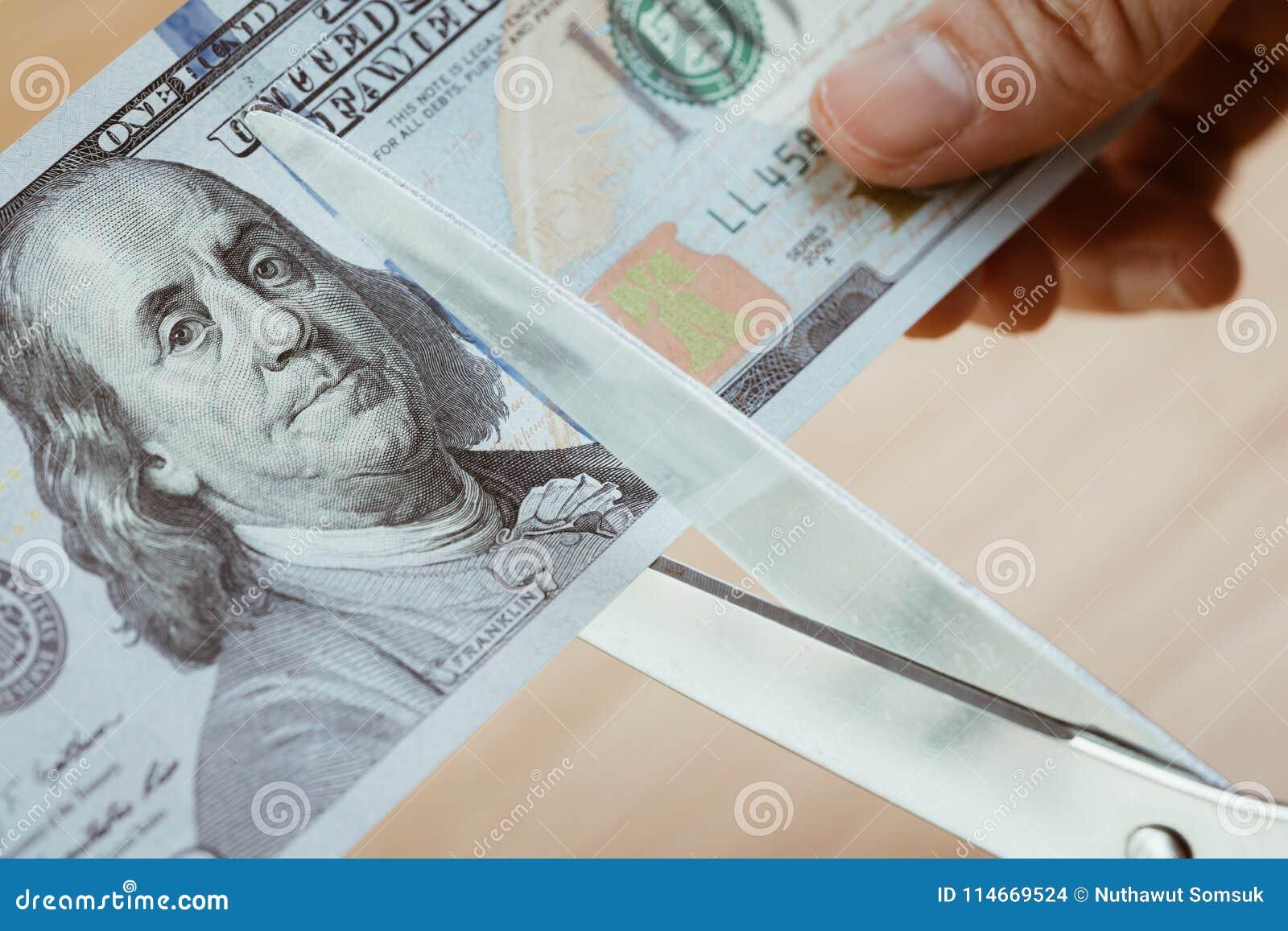 Kobiety ręki mienia nożyce ciie dolarów amerykańskich banknoty, cięcie pączek