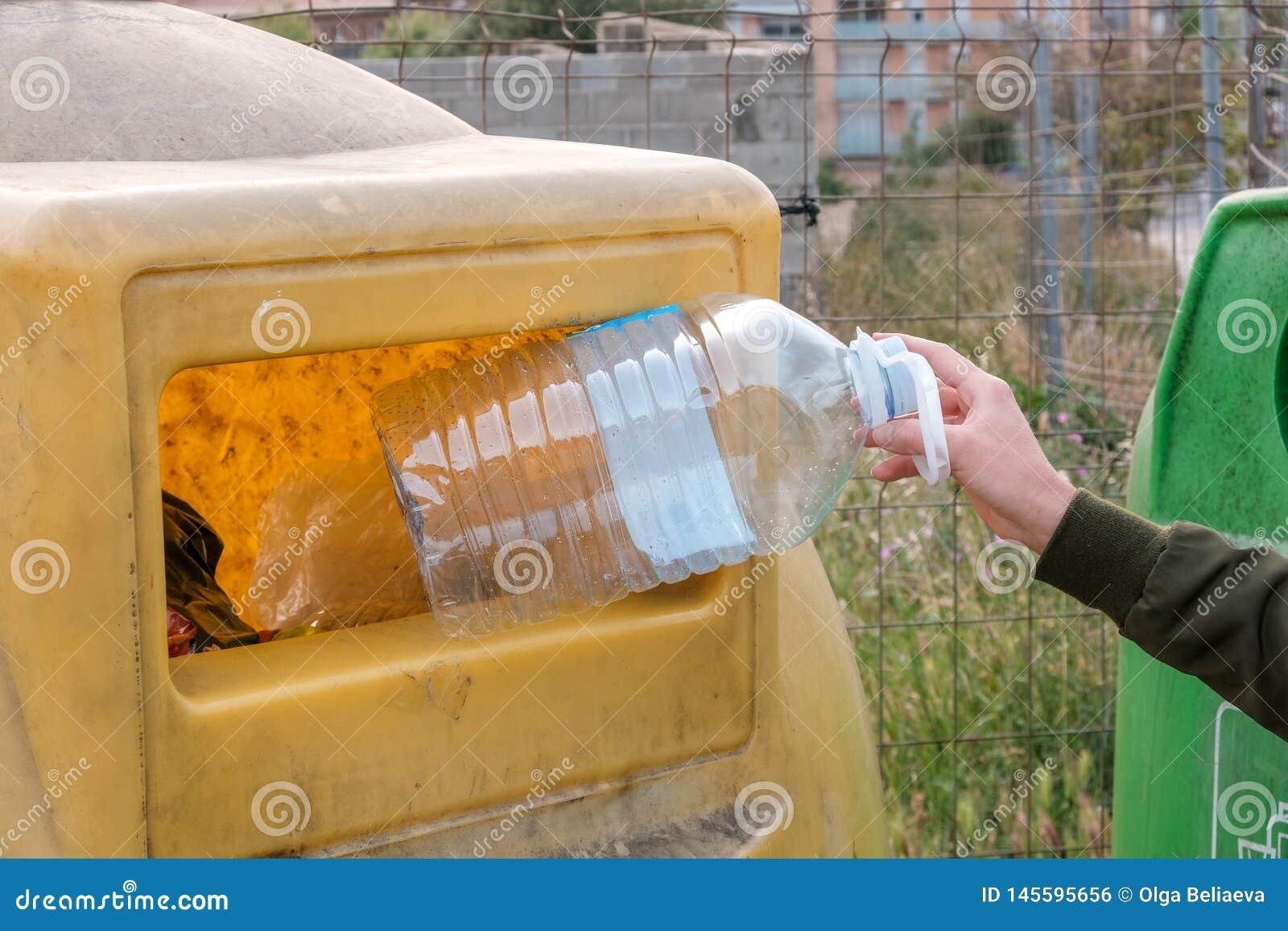 Kobiety ręki mienia pusta duża plastikowa butelka w zbiornika