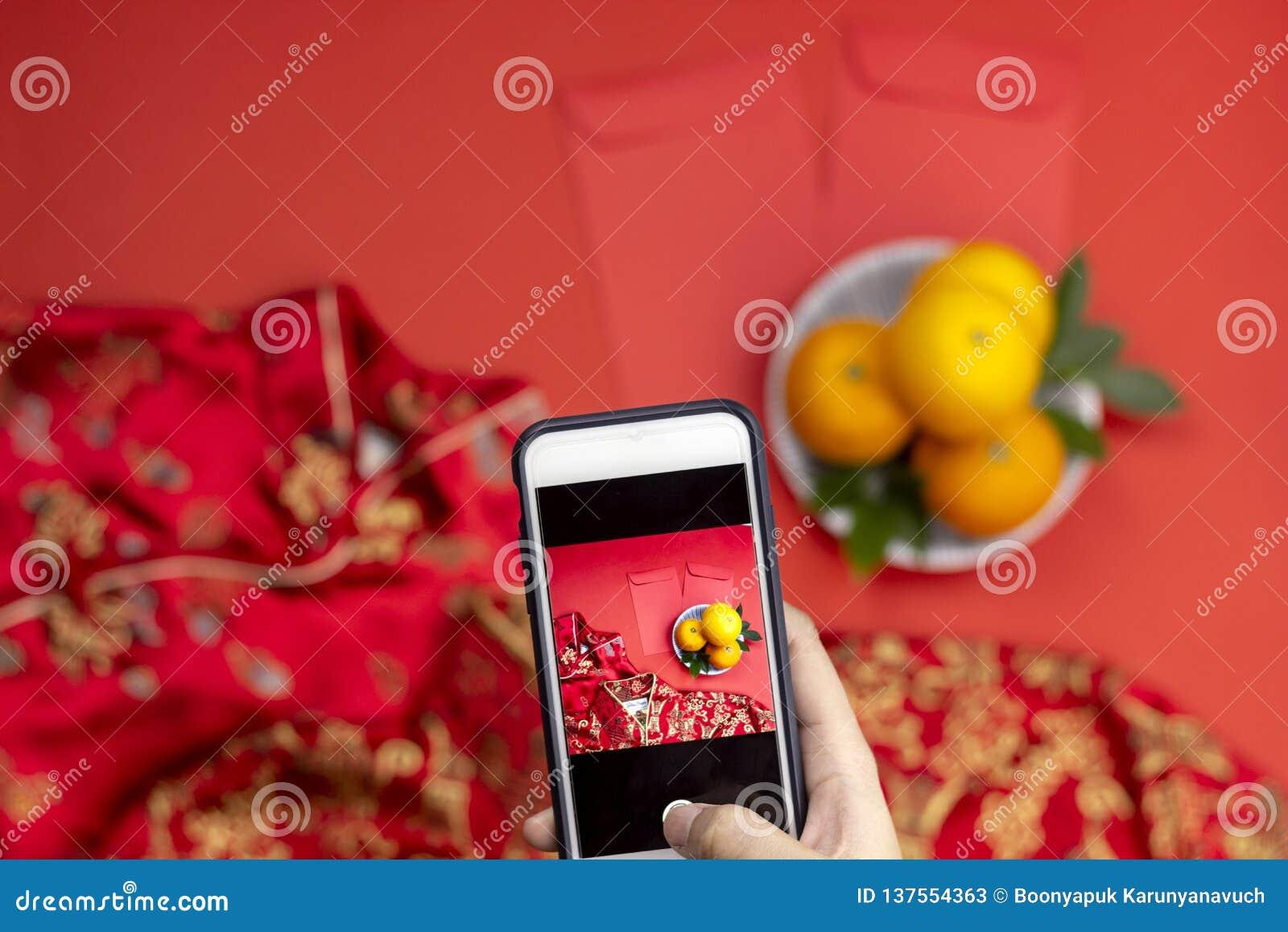 Kobiety ręki mienia smartphone zdobycza nowego roku pomarańcz angpao qipao i kieszeni Chińskie suknie