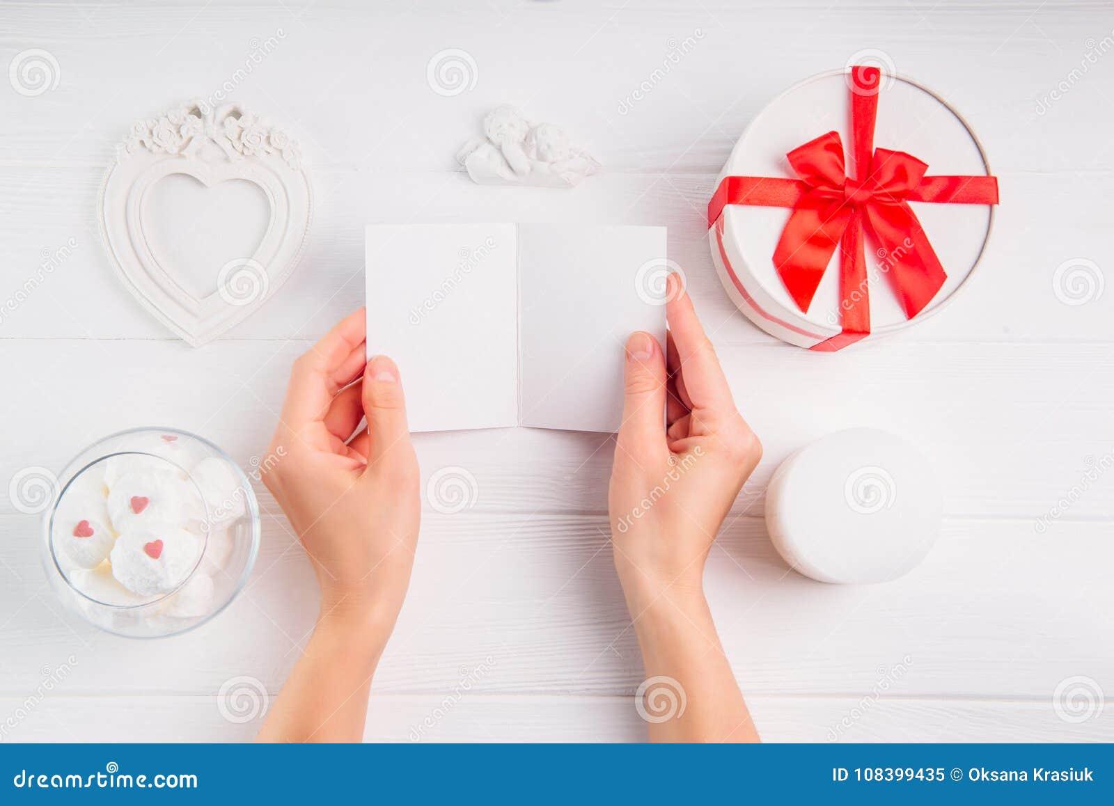 Kobiety ` s ręki trzyma pustego kartka z pozdrowieniami na białym tle z romantyczną dekoracją jako giftbox, rama w kształcie serc