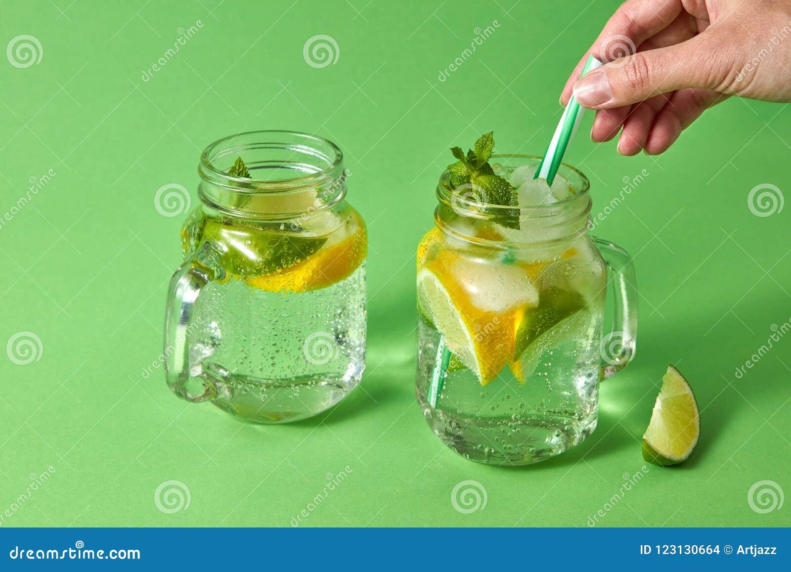 Kobiety ` s ręki wszywek plastikowa słoma w szklanego słój z lemoniadą od naturalnych składników - woda, mennica, plasterki