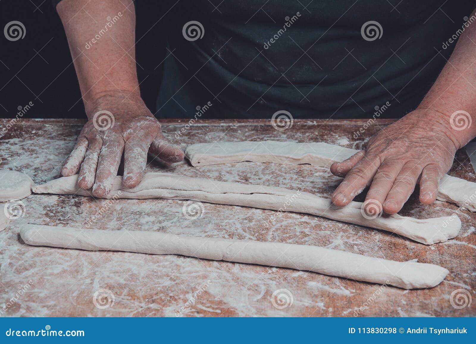 Kobiety starsze rolki z surowego ciasta naleśnikowego dla piec na ciemnym tle