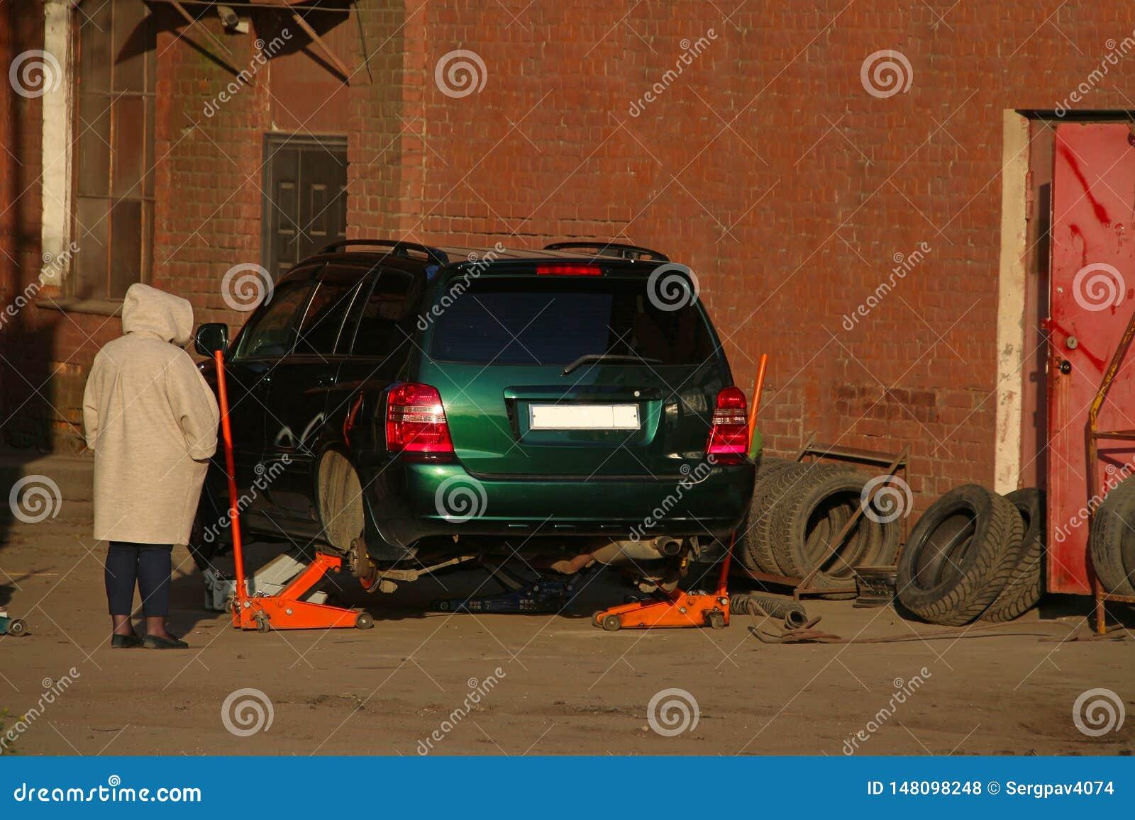 Kobiety stojaki przed jacked w górę samochodu z kołami usuwającymi