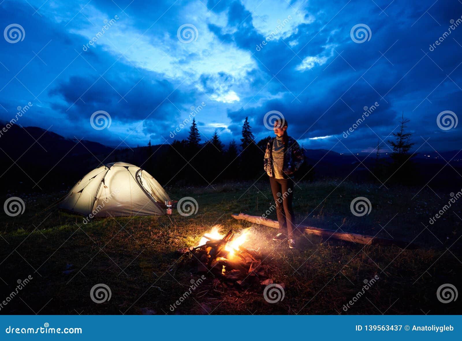 Kobiety turystyczny odpoczywać przy noc campingiem w górach zbliża ognisko i namiot pod evening chmurnego niebo