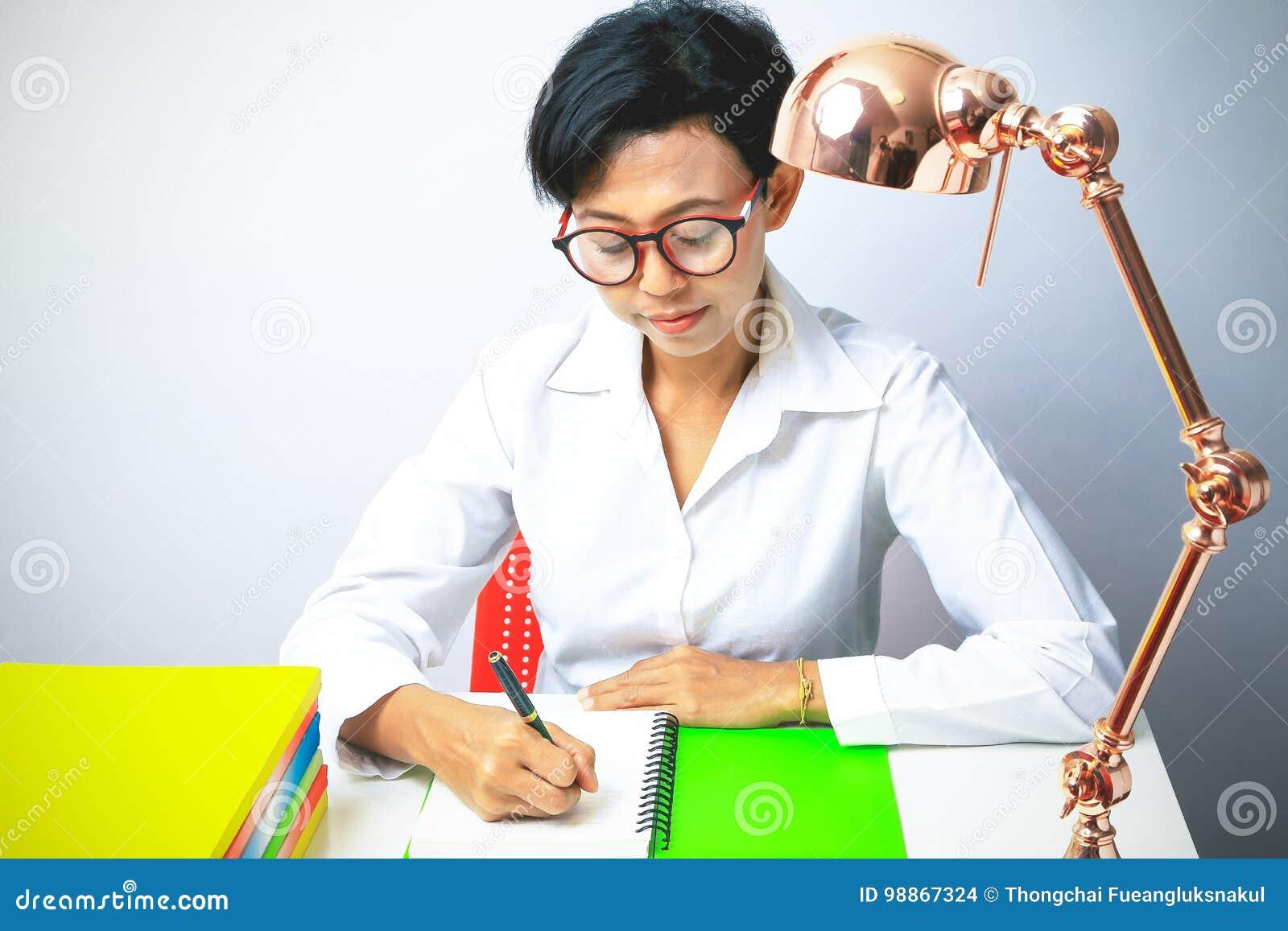 Kobiety writing w ślimakowatym notepad umieszczającym na jaskrawym desktop
