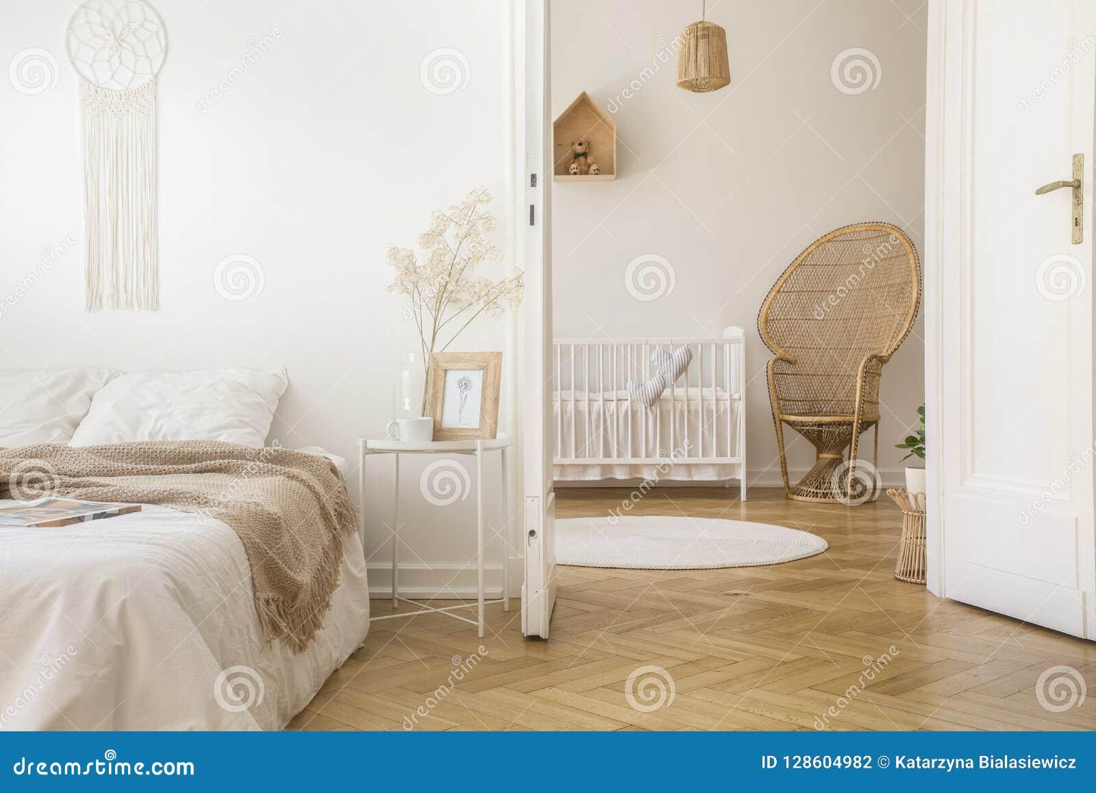 Koc na białym łóżku w sypialni wnętrzu z pawim krzesłem obok dziecka ` s kołyski