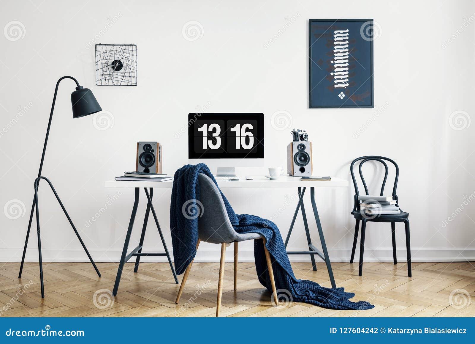 Koc na krześle przy biurkiem z komputerem stacjonarnym w workspace wnętrzu z plakatami i lampą Istna fotografia