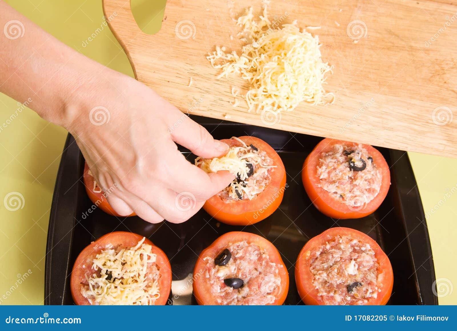 Koch fügt Käse angefüllter Tomate hinzu