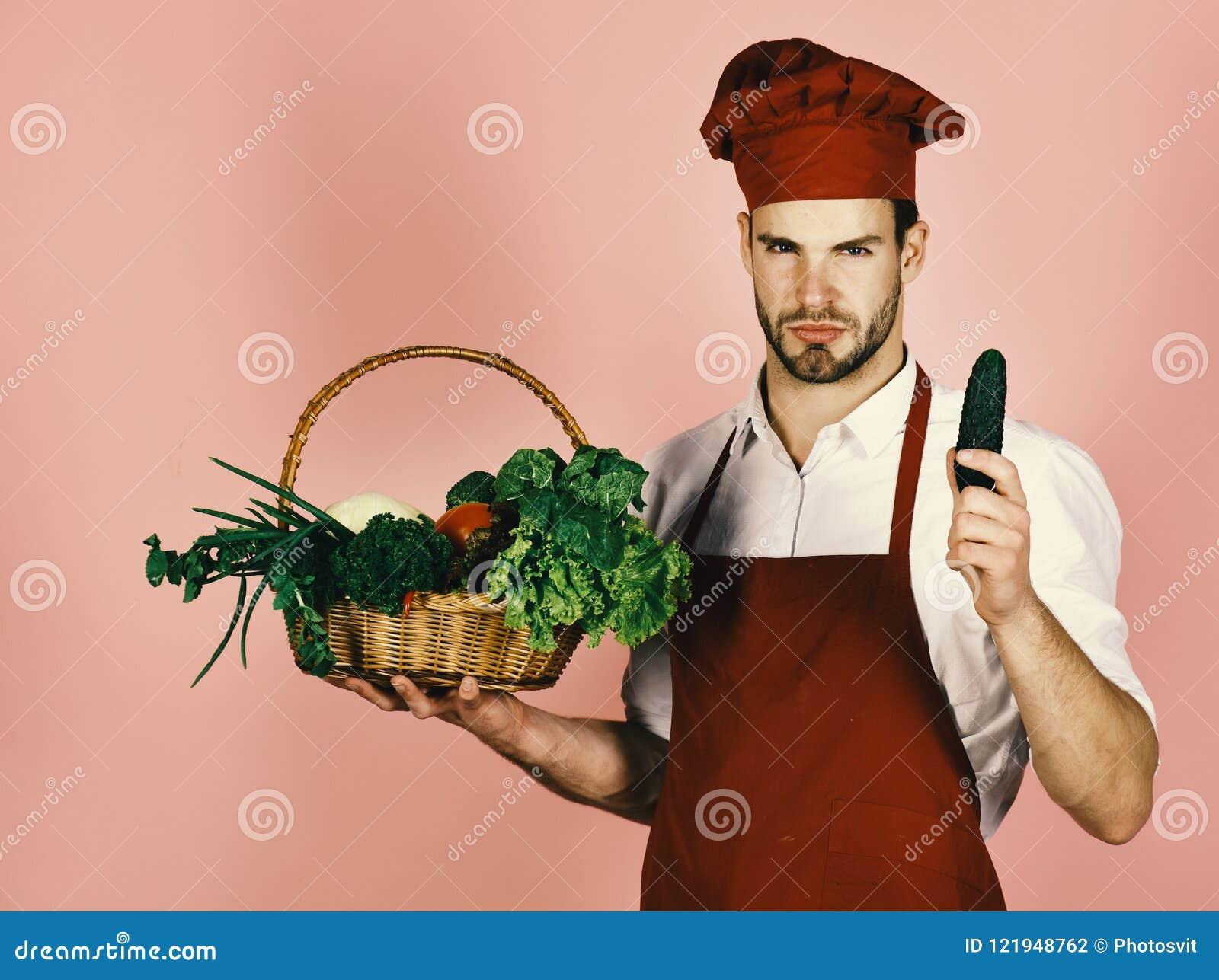 Koch mit strengem Gesicht hält Gurke und Weidenkorb von frischen Veggies Chef in Burgunder-Uniform hält Gurke