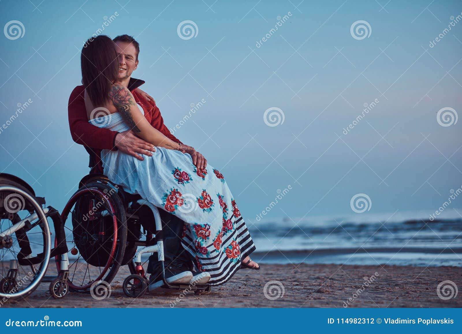 Kochająca para, kobieta siedzi na jej męża ` s podołku, odpoczywa na plaży przeciw tłu jaskrawy świt