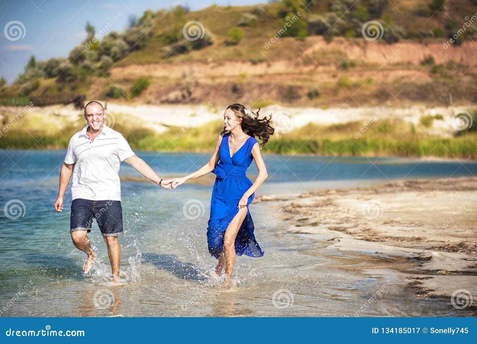 Kochająca para na brzeg jezioro morza bieg wzdłuż wody W miłości lata bieg na morzu z pluśnięciami woda Miłość