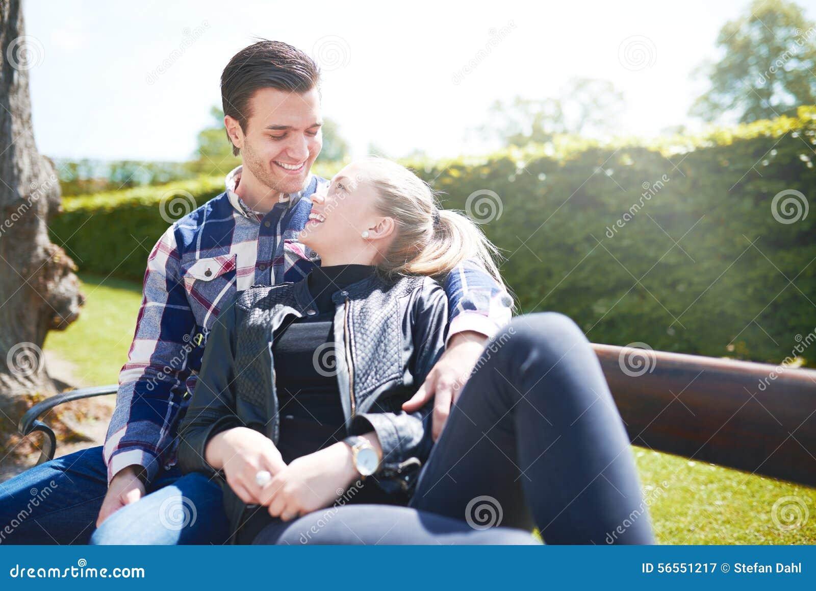 Kochająca para relaksuje na parkowej ławce