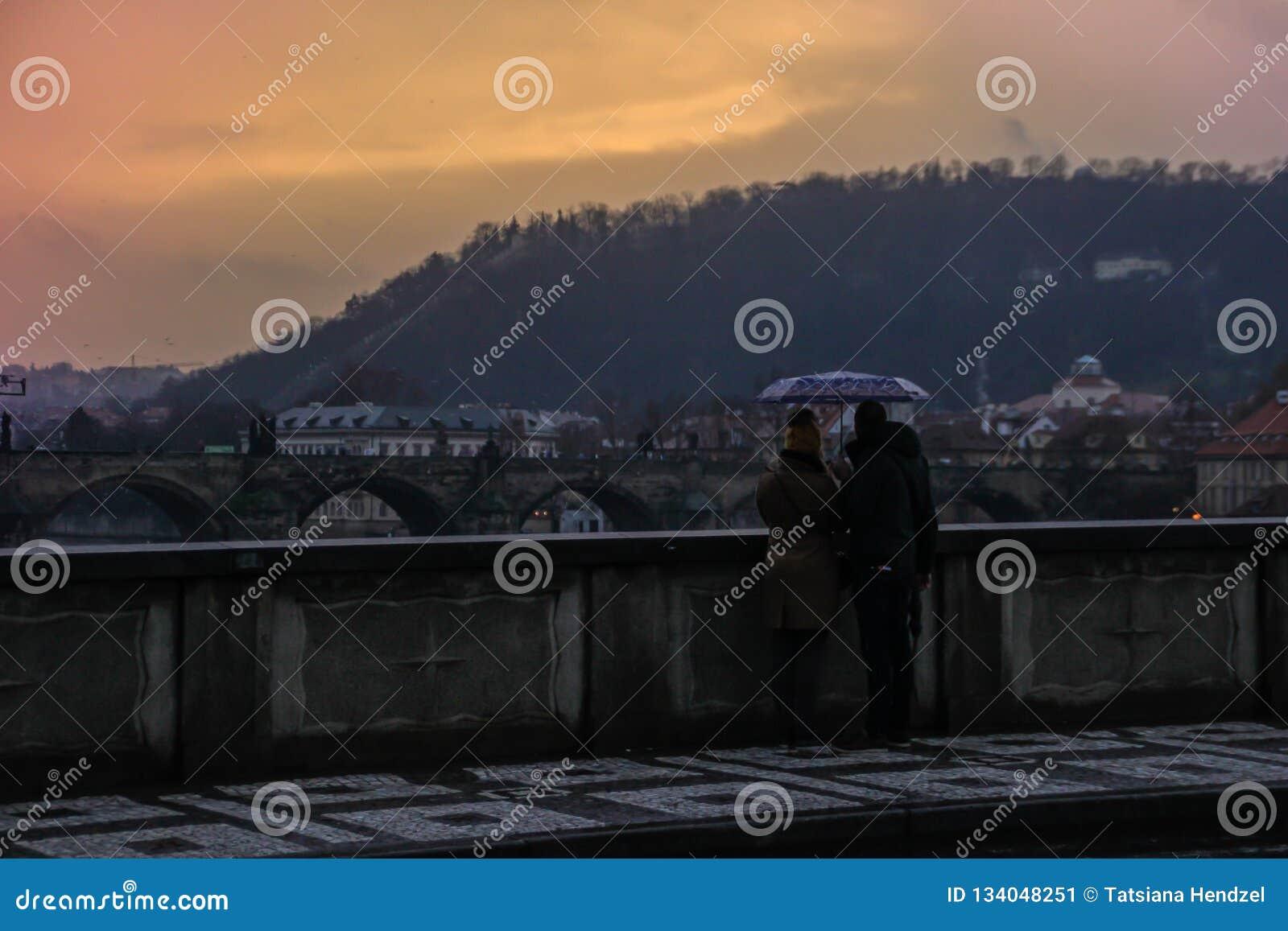 Kochająca pary pozycja pod parasolem z widokiem Charles mostu w deszczu przy zmierzchem