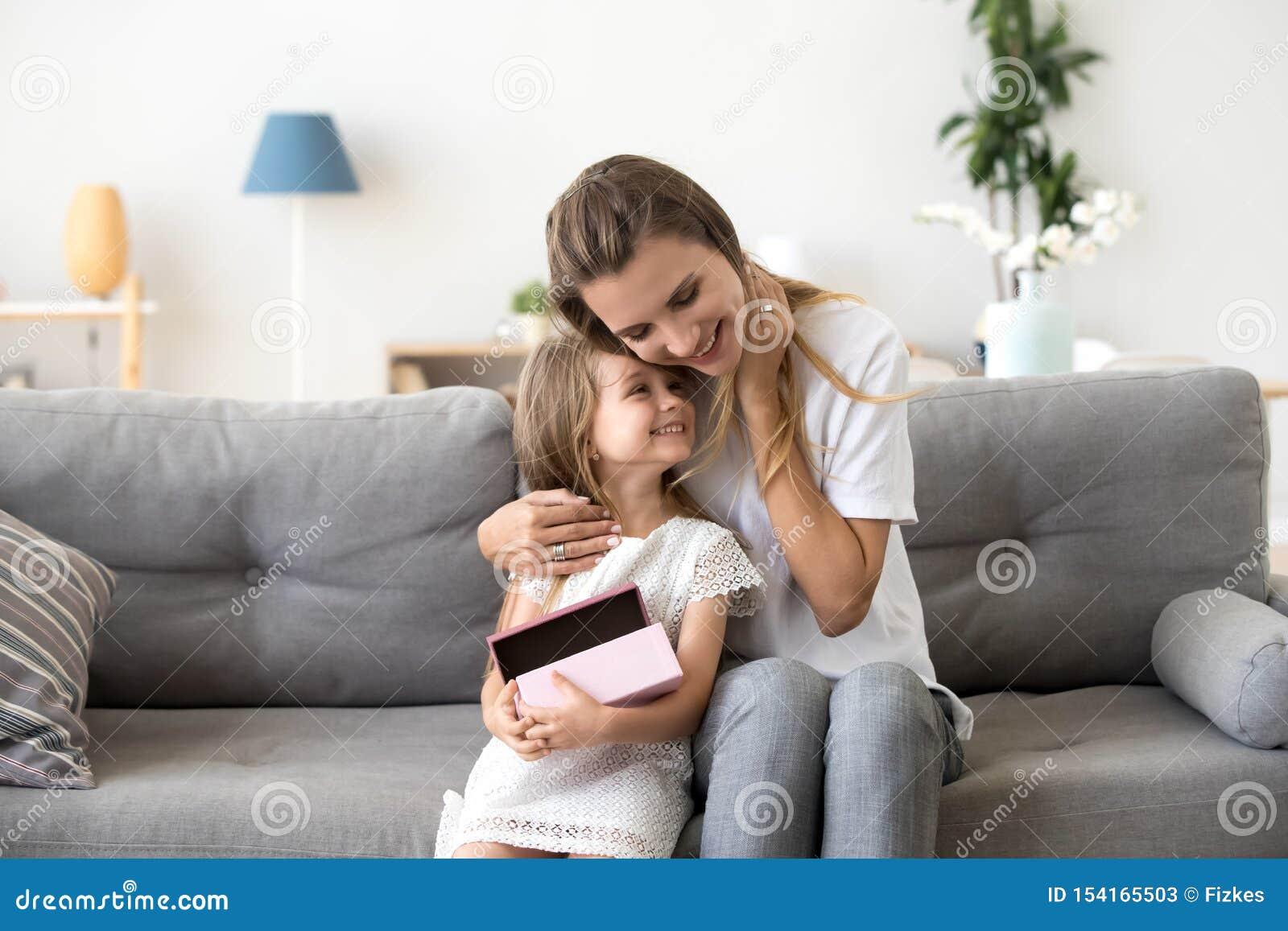 Kochającego macierzystego przytulenia mała córka siedzi wpólnie na kanapie