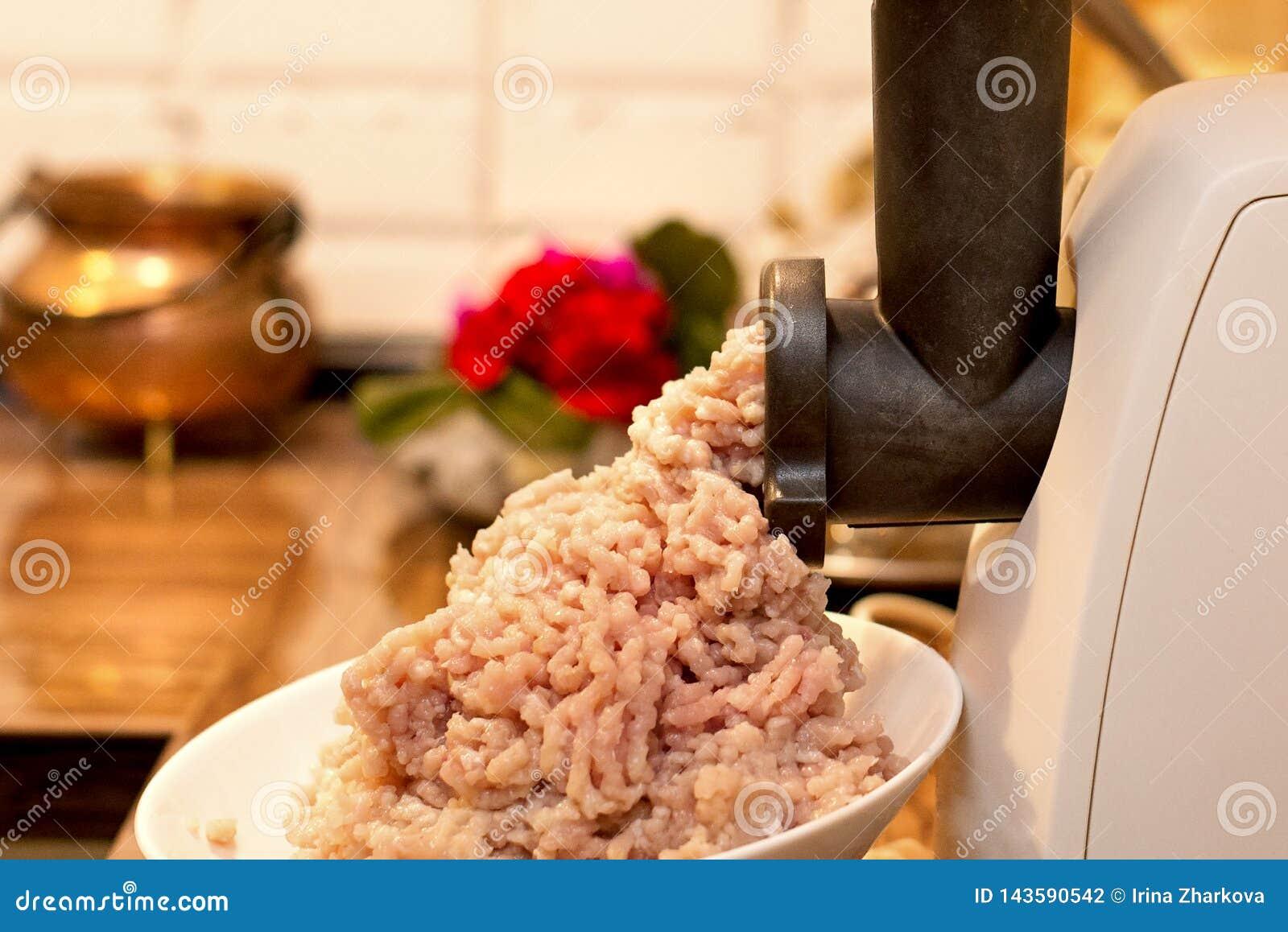 Kochen des Hackfleischs in einem elektrischen Fleischwolf auf dem K?chentisch