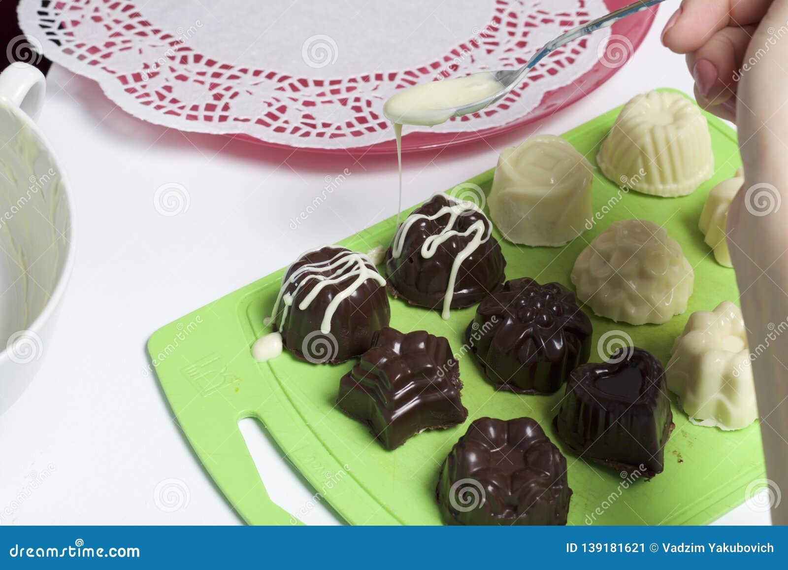 Kochen von Bonbons mit Kokosnuss und Kondensmilch In einer Glasur der weißen und schwarzen Schokolade