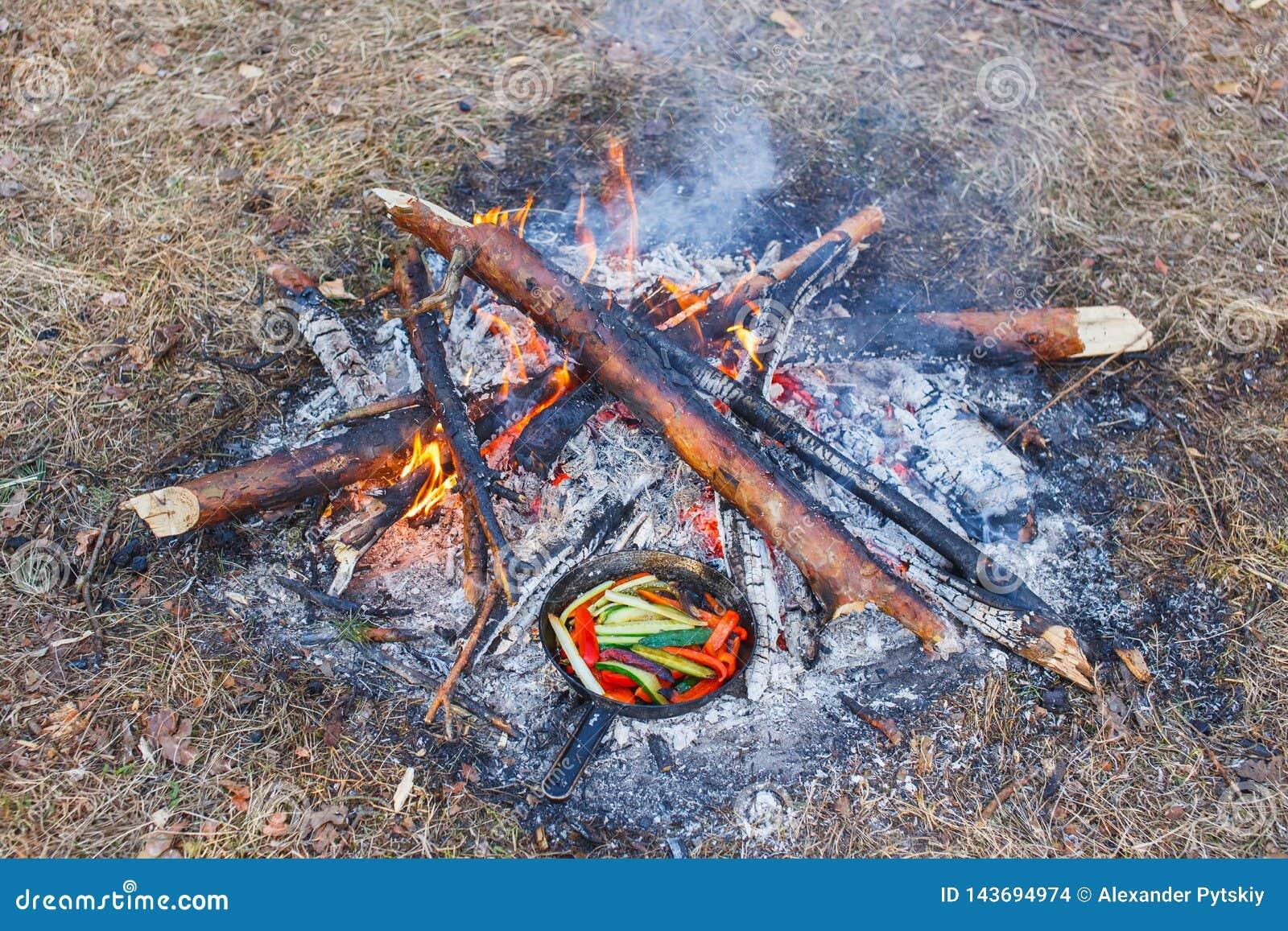 Kochen von Gerichten vom roten grünen Pfeffer und den Gurken in einer Wanne auf einem Feuer