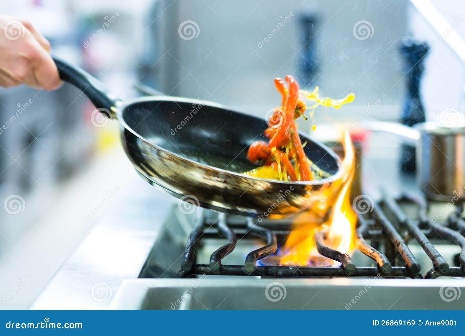 Kock i restaurangkök på ugnen med pannan