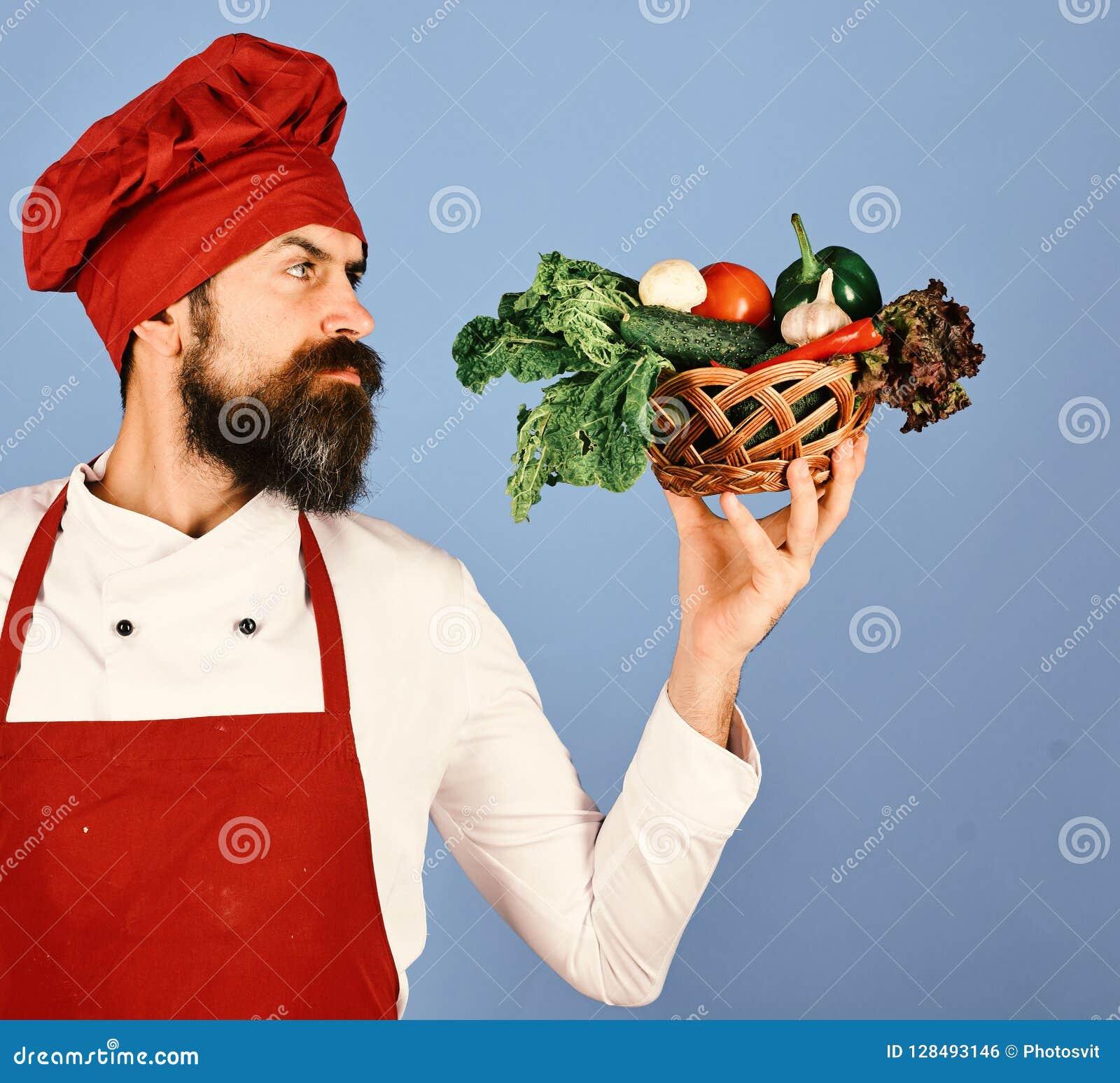 Kock som rymmer en bunke full av rå nya organiska grönsaker