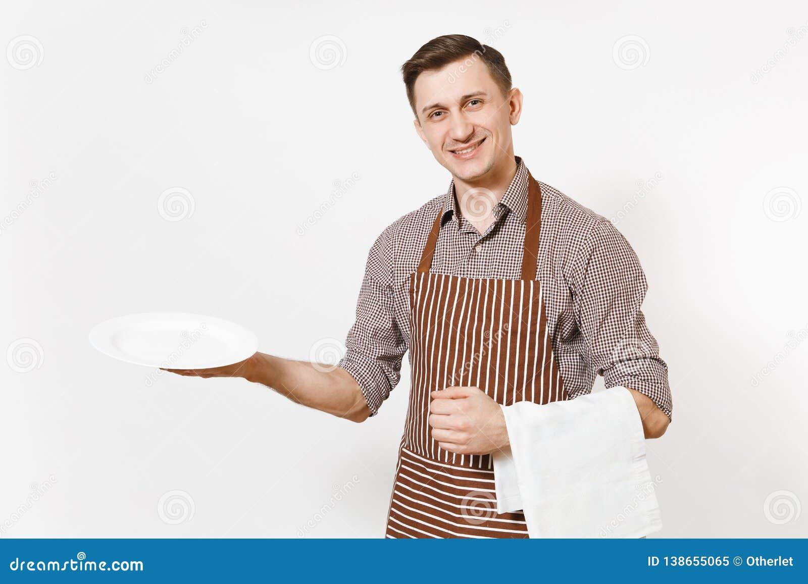 Kocken eller uppassaren för ung man i det randiga bruna förklädet, skjortan som rymmer den vita runda tomma klara plattan, handdu