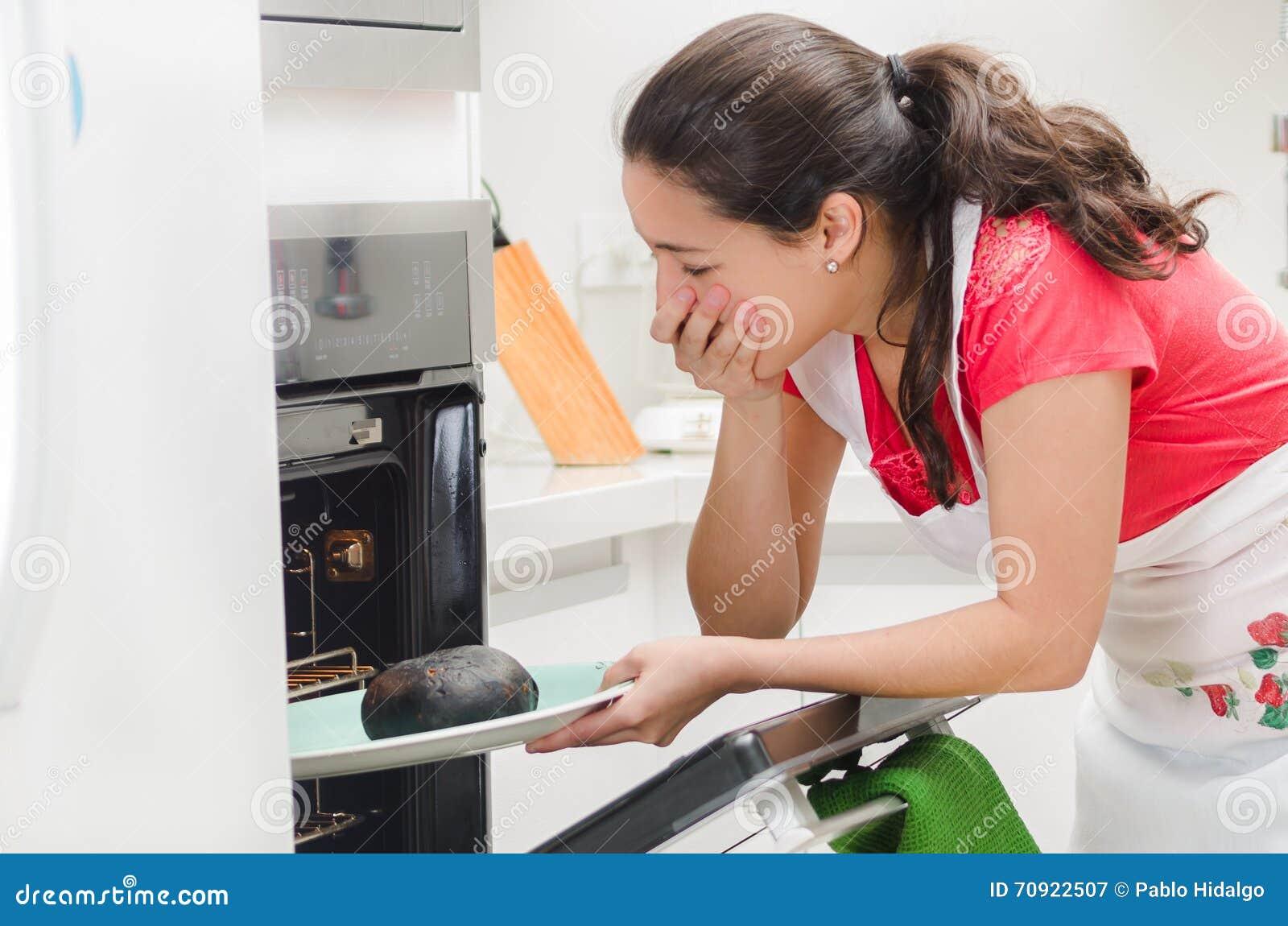 Kocken för den unga kvinnan som ser in i ugnen med frustrerat ansiktsuttryck som rymmer svart, brände bröd på magasinet