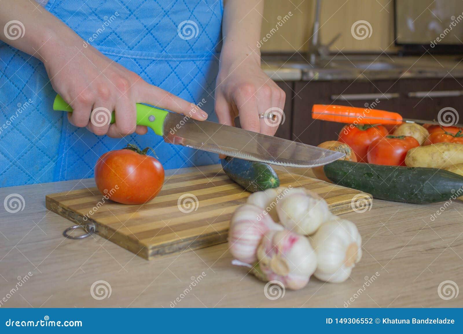 Kocken klipper gr?nsakerna in i ett m?l En kvinna anv?nder en kniv och kockar Kvinnas h?nder som klipper gr?nsaker, bak nya gr?ns