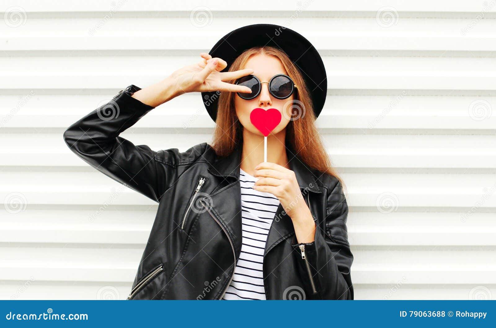 Koel jong meisje met rood lollyhart die het leerjasje van de manier zwart hoed over witte stedelijk dragen