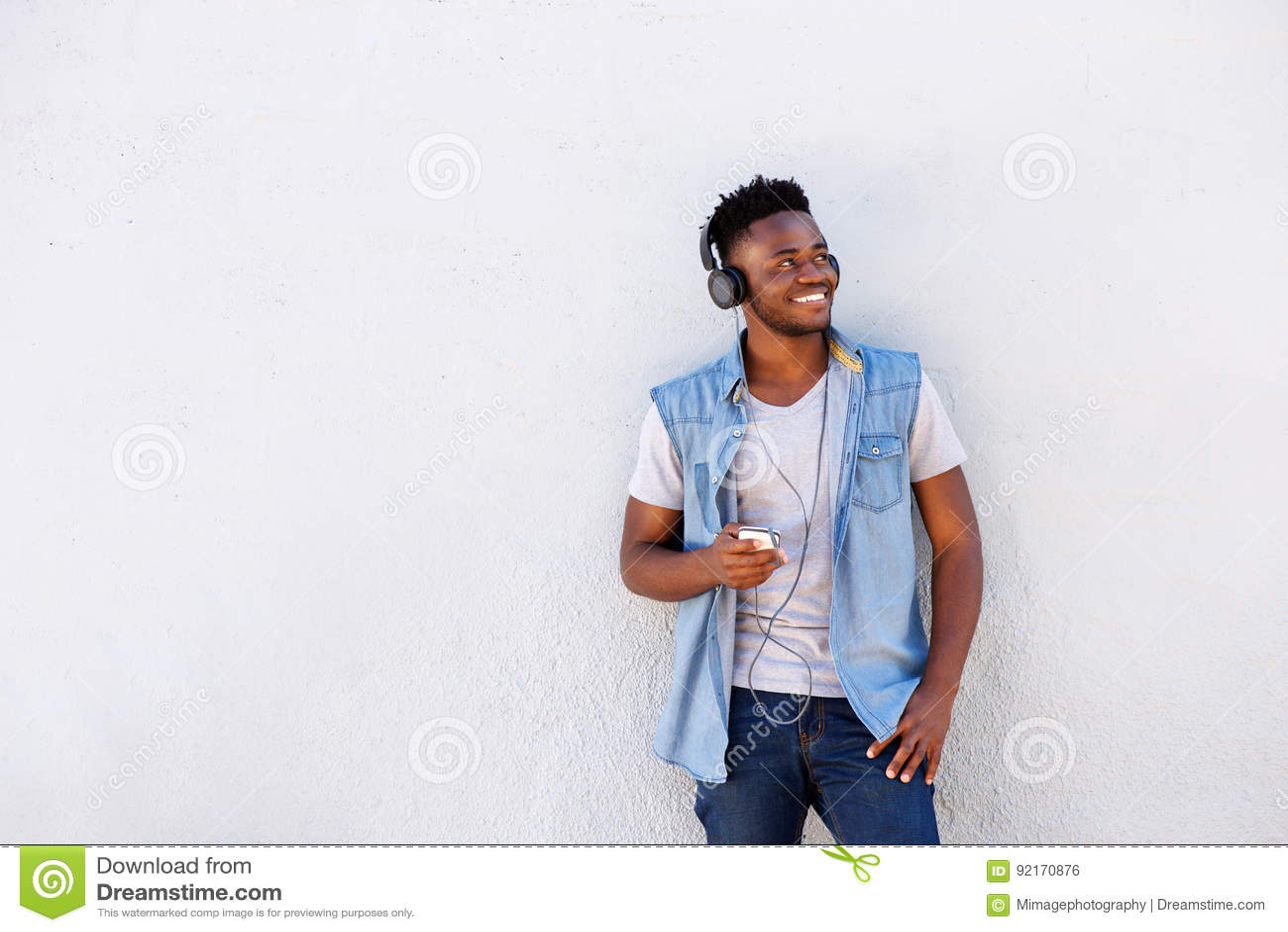 Koele Afrikaanse kerel met mobiele telefoon en hoofdtelefoons die aan muziek luisteren